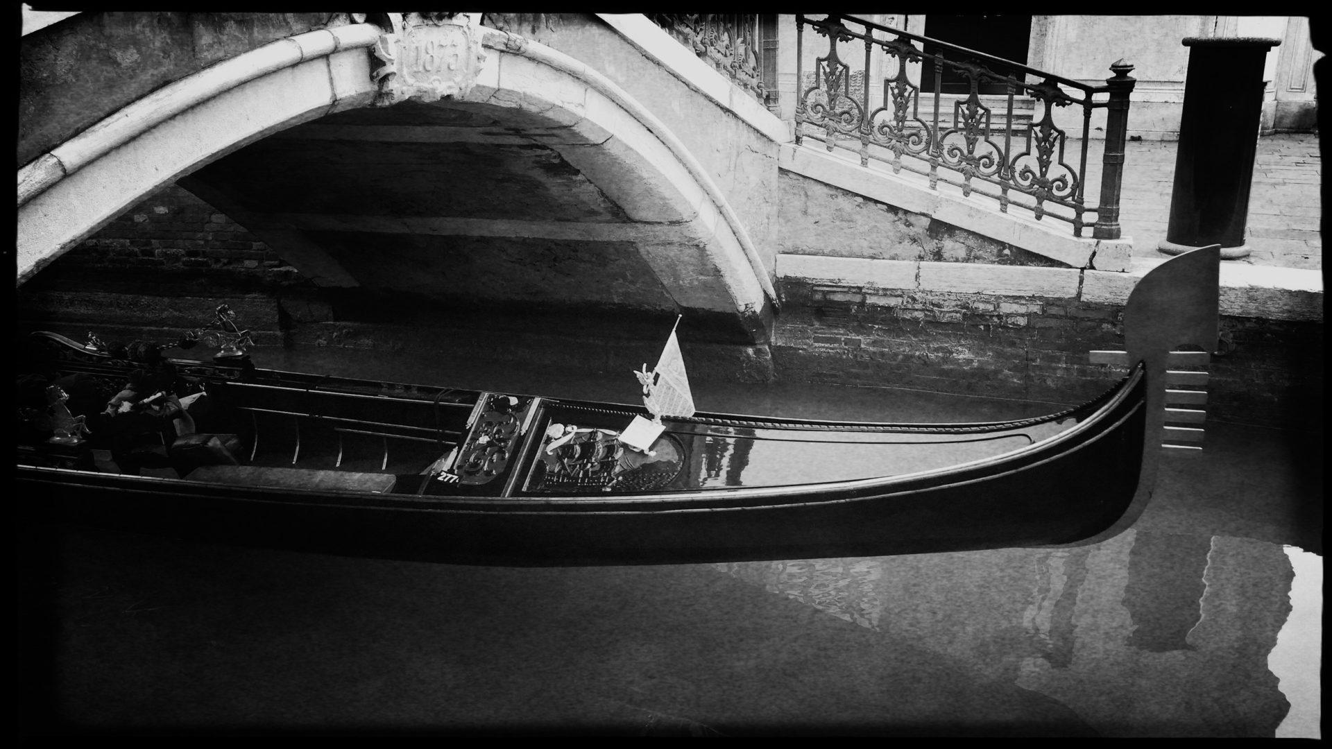 Gondel kommt unter einer Brücke in Venedig hervor