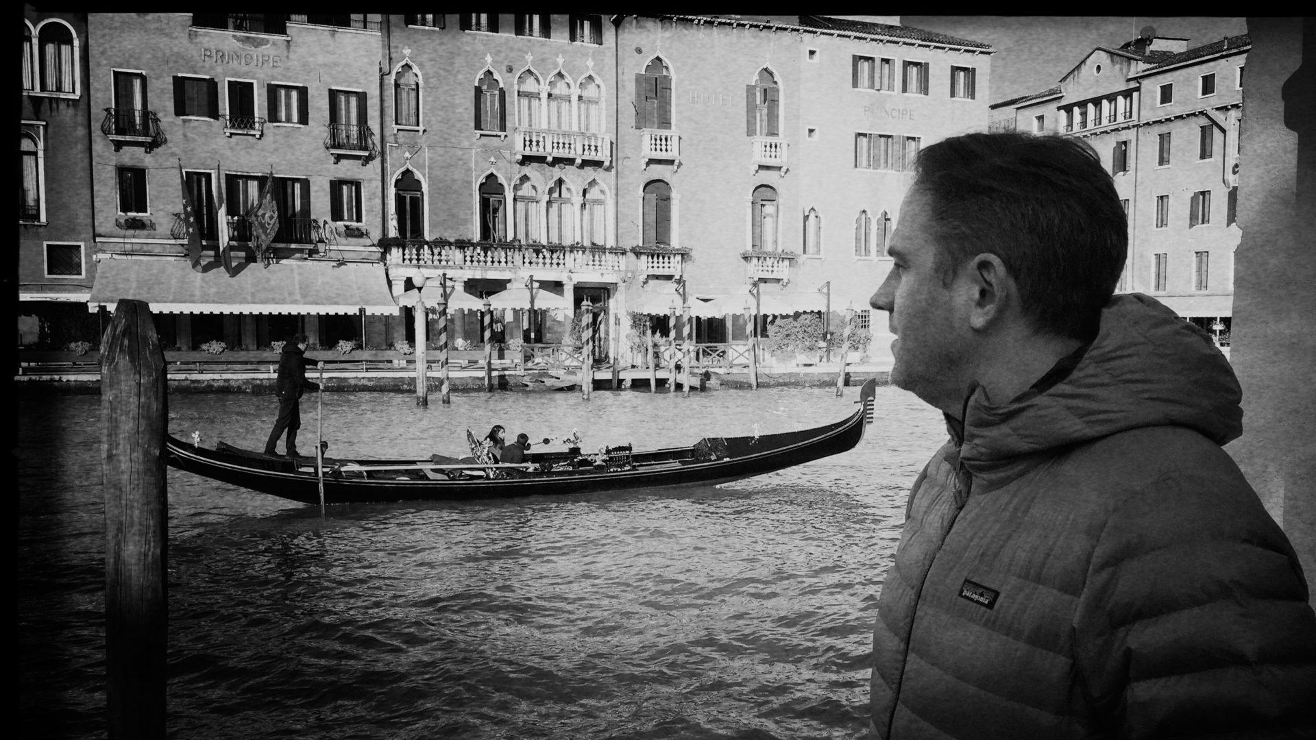 Mann schaut auf Gondel und Palazzo am Canale Grande in Venedig
