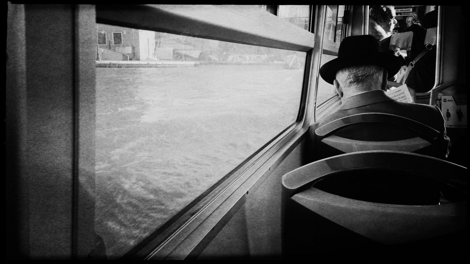 Mann mit Hut liest Tageszeitung im Vaporetto von Venedig