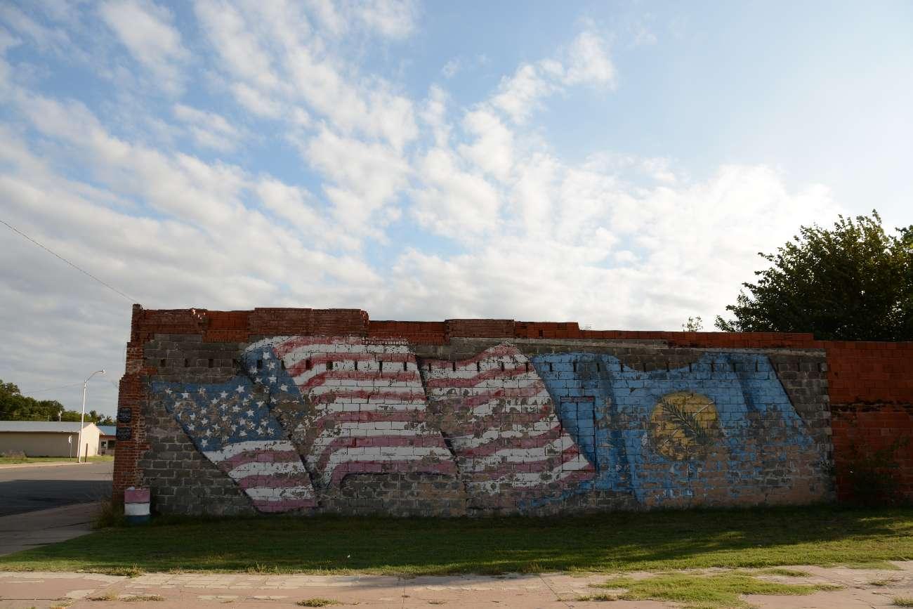 Verblichene amerikanische Flagge auf einer Hauswand in Erick, Oklahoma