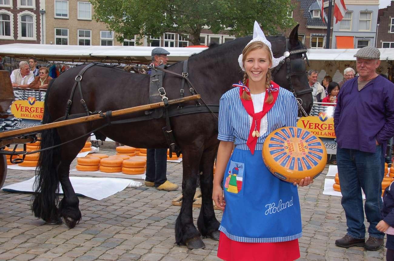 Frau Antje mit Käserad und Pferdekutsche im Hintergrund