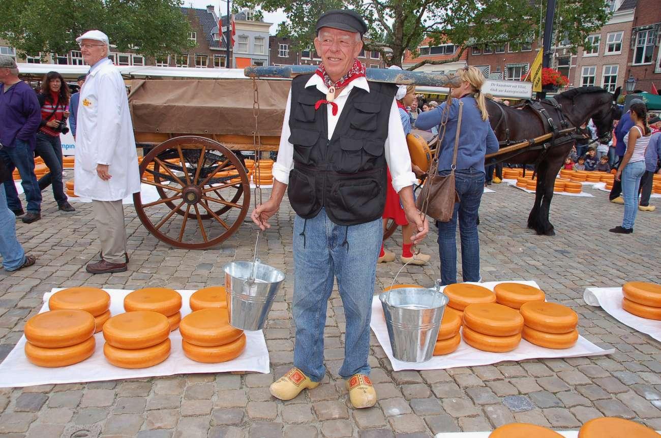 Milchbauer mit Eimer vor Käserädern in Gouda