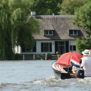 Ein Mann mit Hut einsam in einem Boot auf der Vecht in Holland