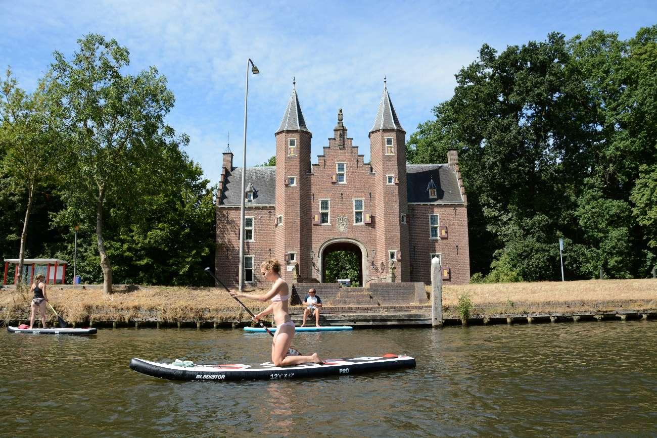 Stand-up-Padddlerin auf der Vecht vor einem kleinen Schloss in Holland