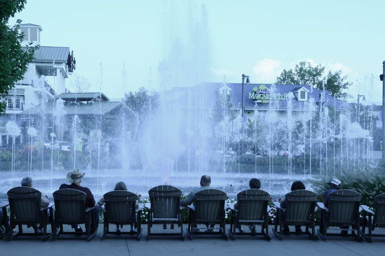Einträchtig betrachten genügsame Amerikaner in Adirondack-Stühlen einen Springbrunnen