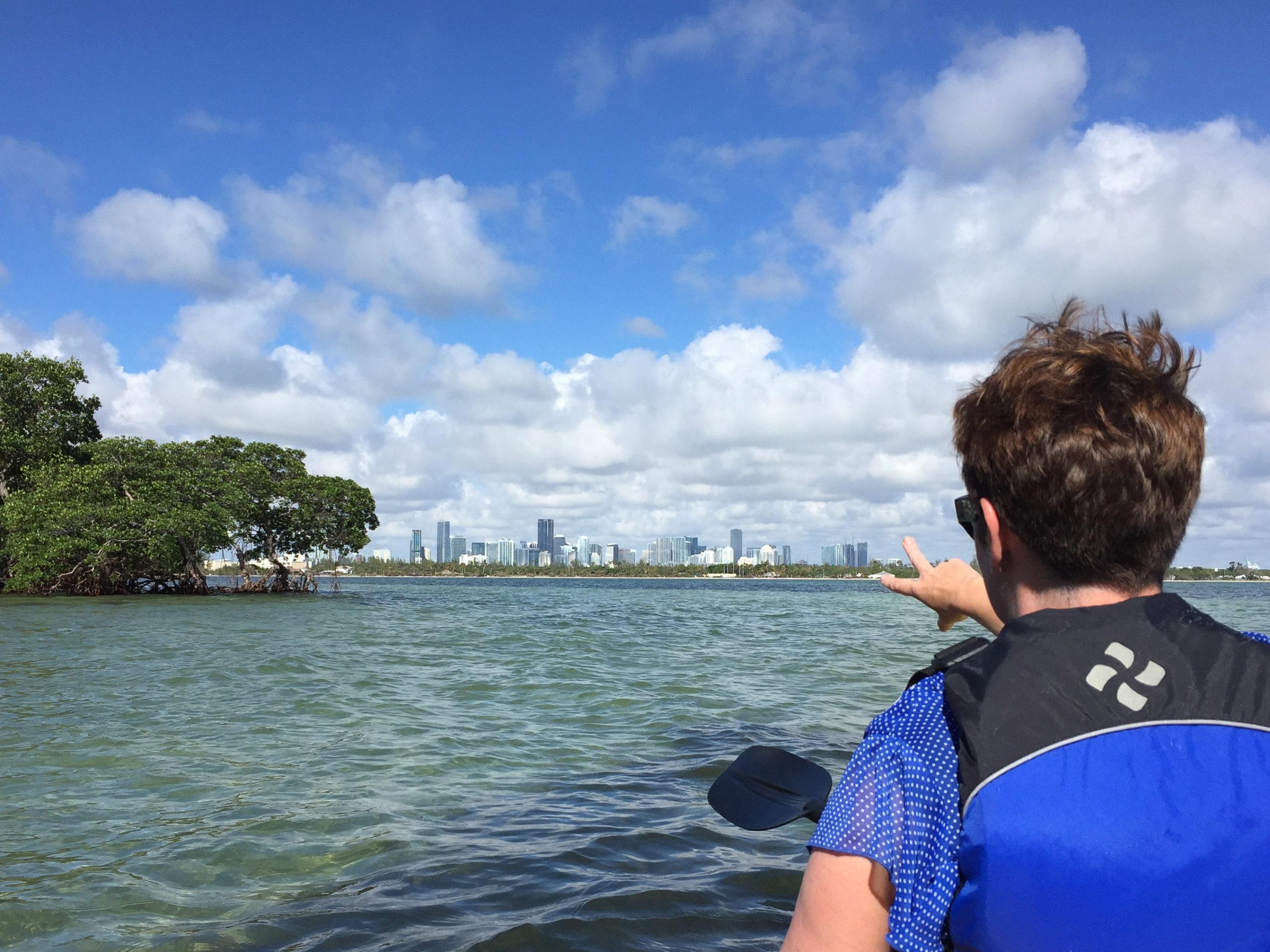 Eine Frau zeigt aus einen Kanu auf die Wolkenkratzer von Miami