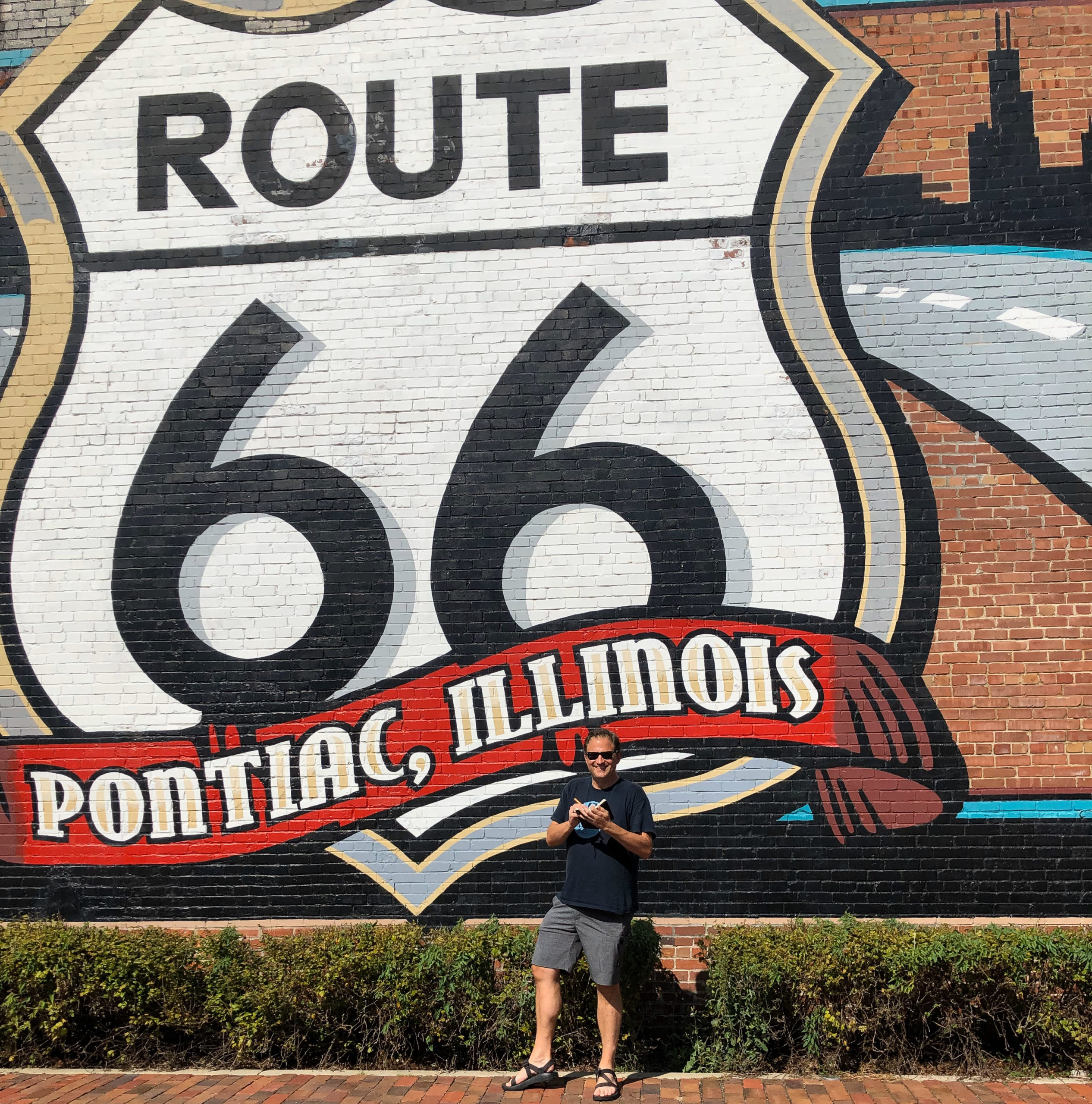 Autor Ralf Johnen vor einem Wandgemälde mit dem Logo der Route 66 in Illinois