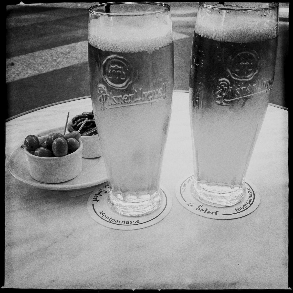 Zwei Biere und Oliven stehen auf dem Tisch des Cafe Le Select in Paris
