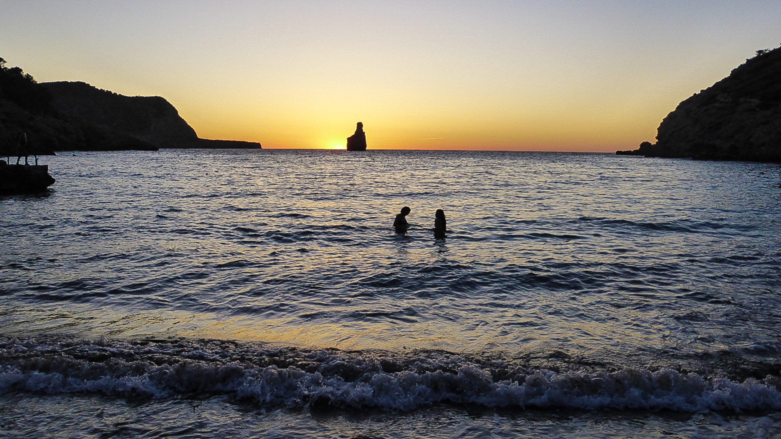 Der Moment: Zwei Frauen baden zum Sonnenuntergang in der Cala Benirras auf Ibiza