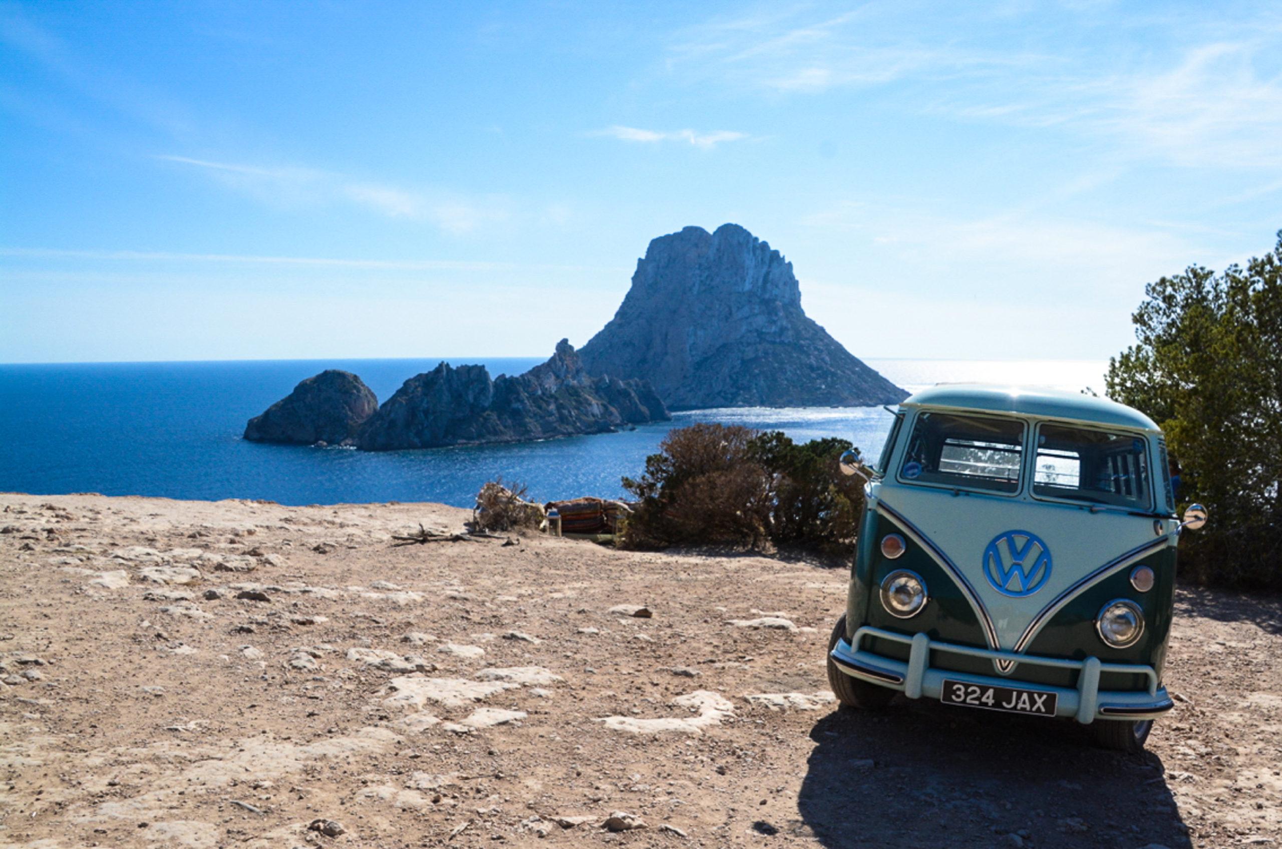 Ein VW Bully auf einem Felsen mit Blick auf Es Vedra auf Ibiza