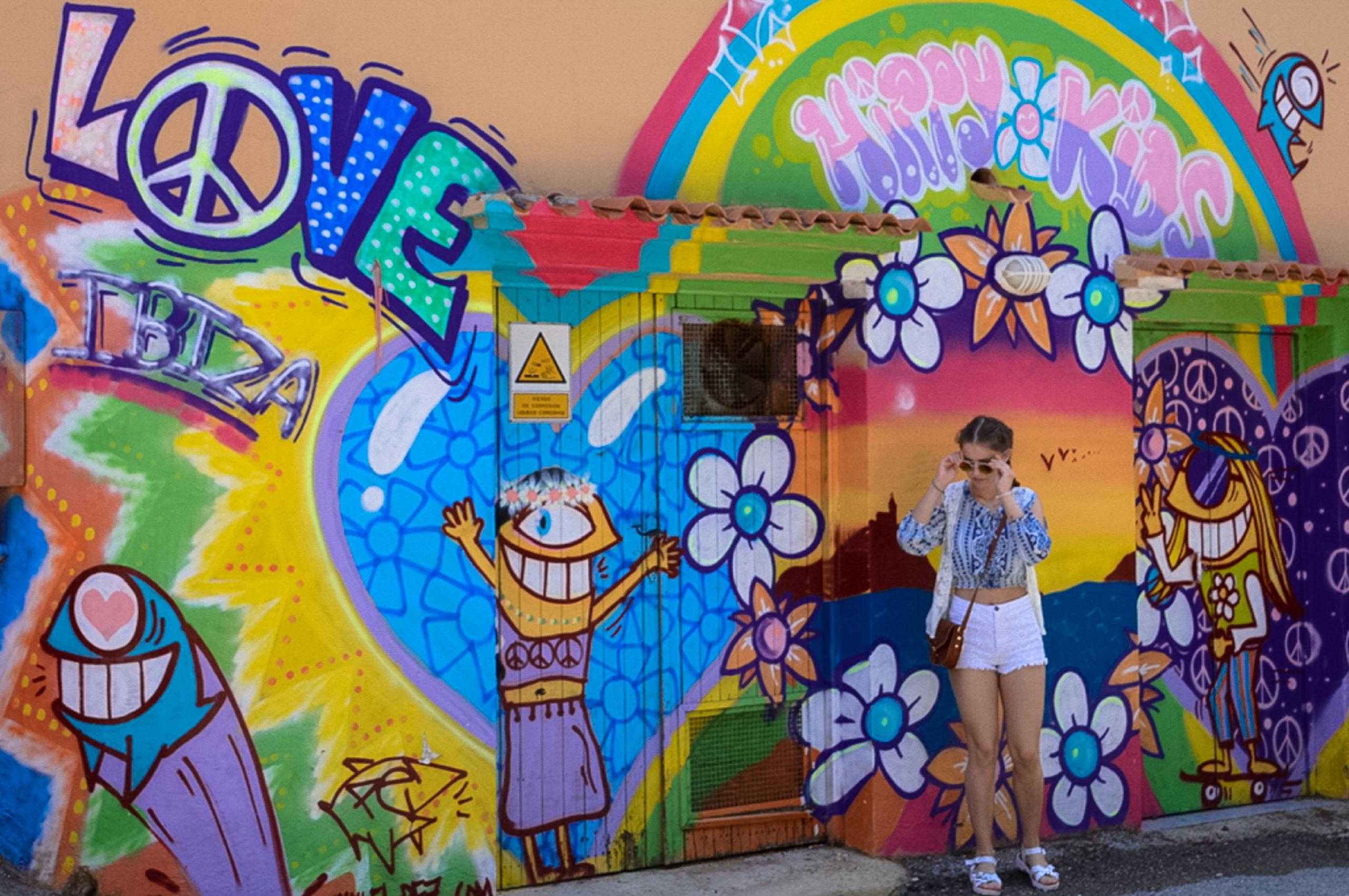 Hippie-Mädchen vor Street Art auf Ibiza