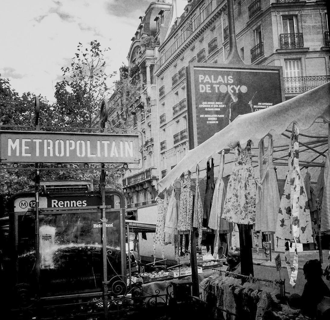 Die Metrostation Rennes in Paris mit einem Marktstand und Bürgerhäusern im Hintergrund