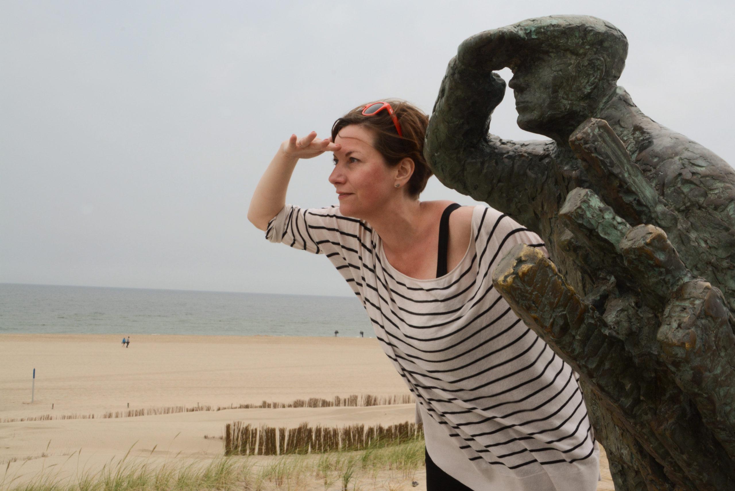 Frau mit Statue am Strand von Camperduin in Nordholland