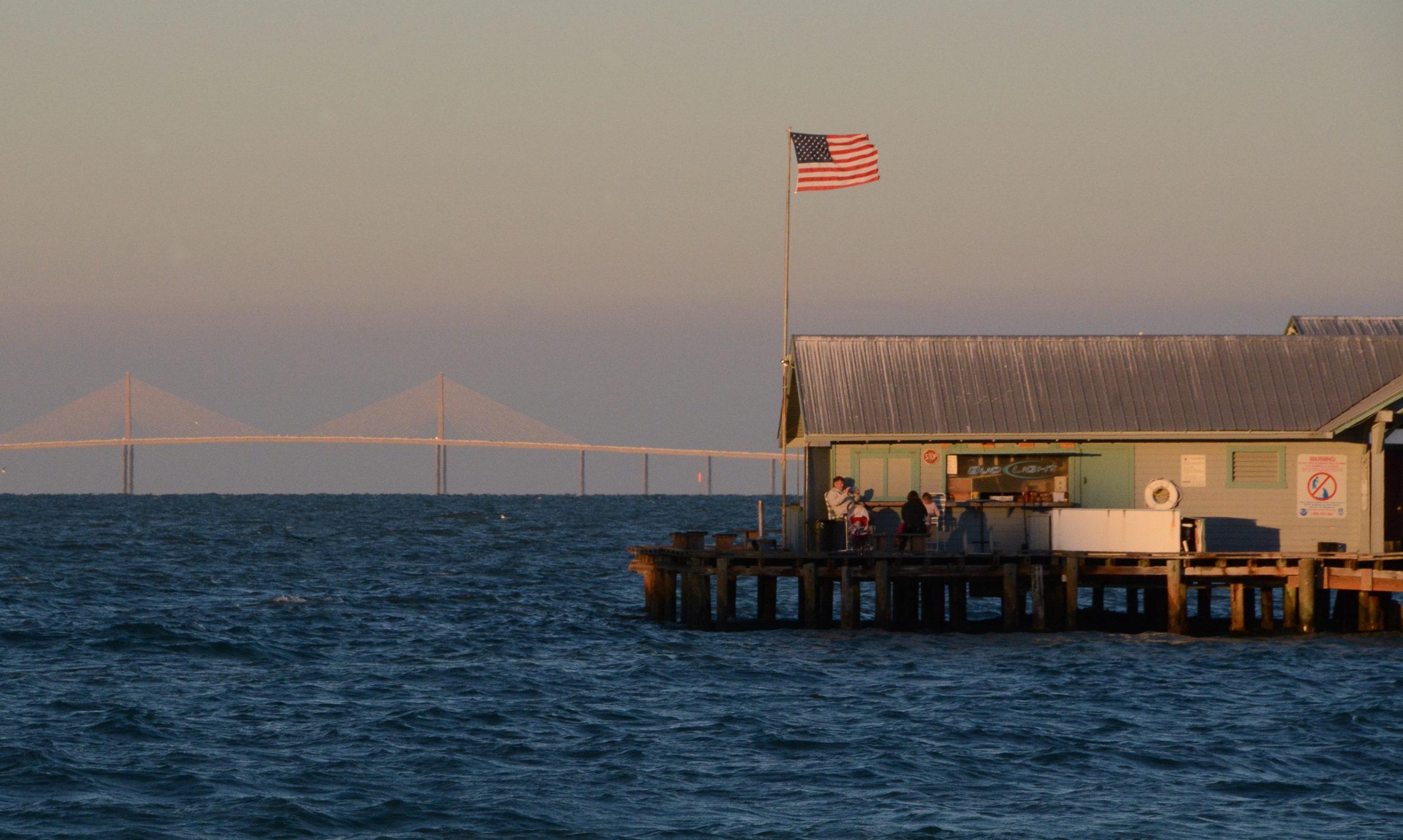 Holzpier in Anna Maria Island mit der Sunshine Skyway Bridge in der Tampa Bay