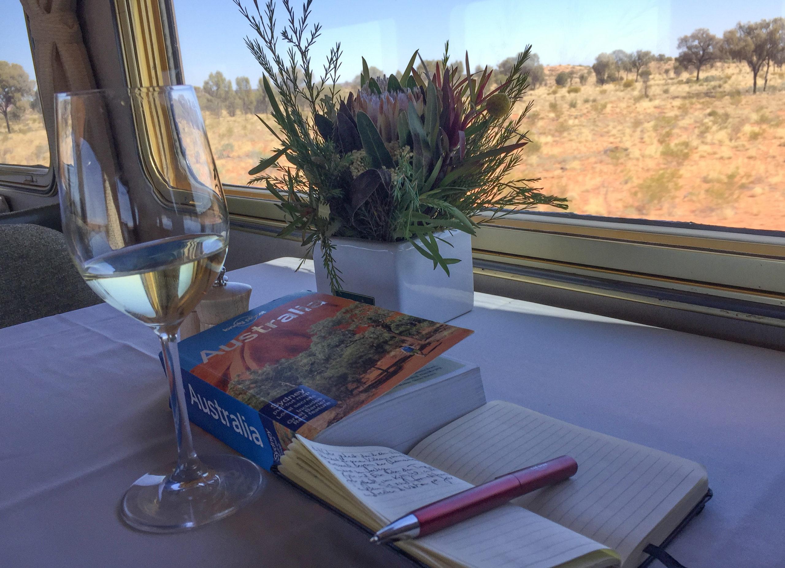 Notibuch, Reiseführer und ein Glas Wein im Speisewagen von The Ghan