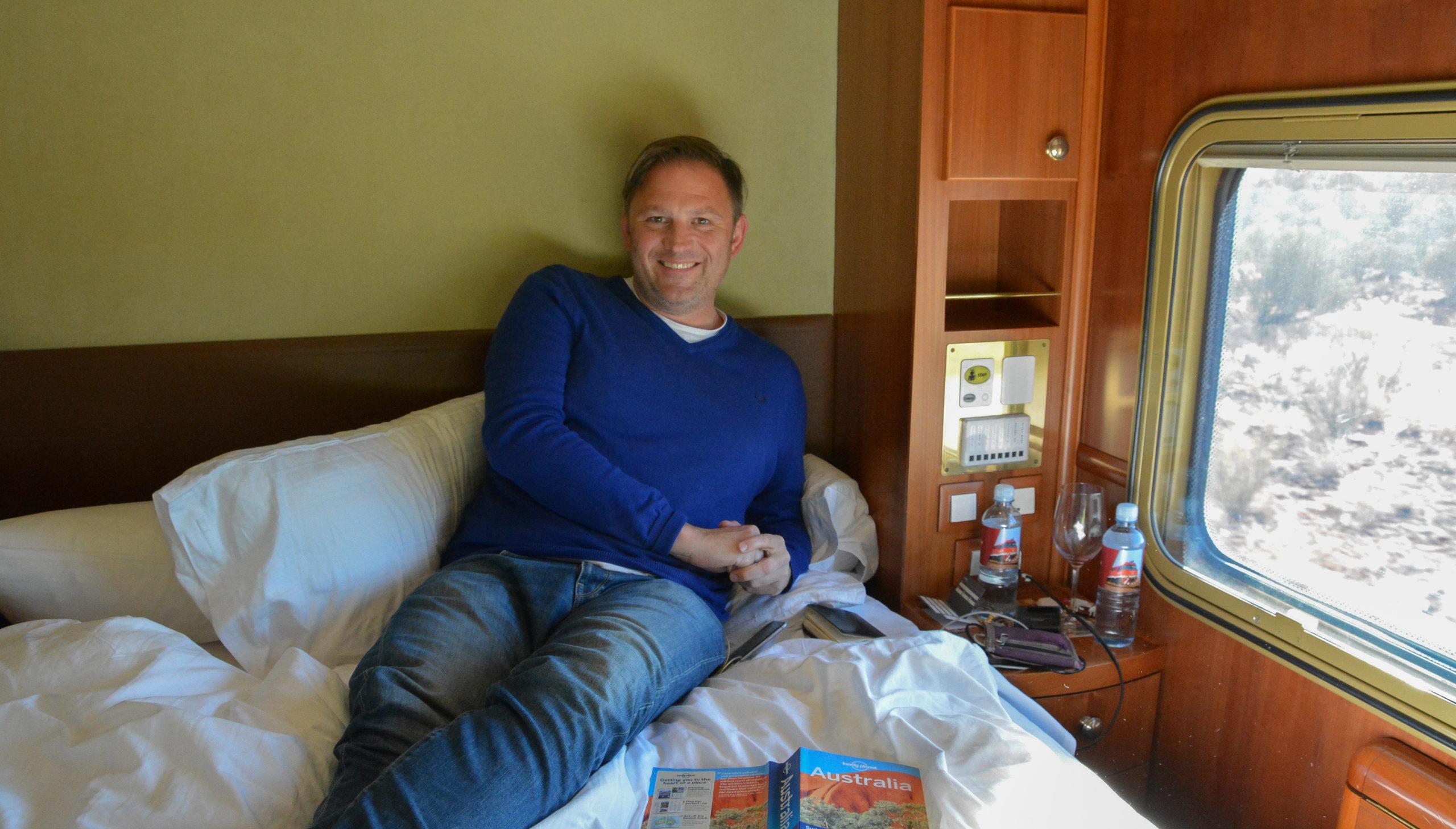 Autor Ralf Johnen auf dem Bett seiner Kabine im Zug The Ghan in Australien