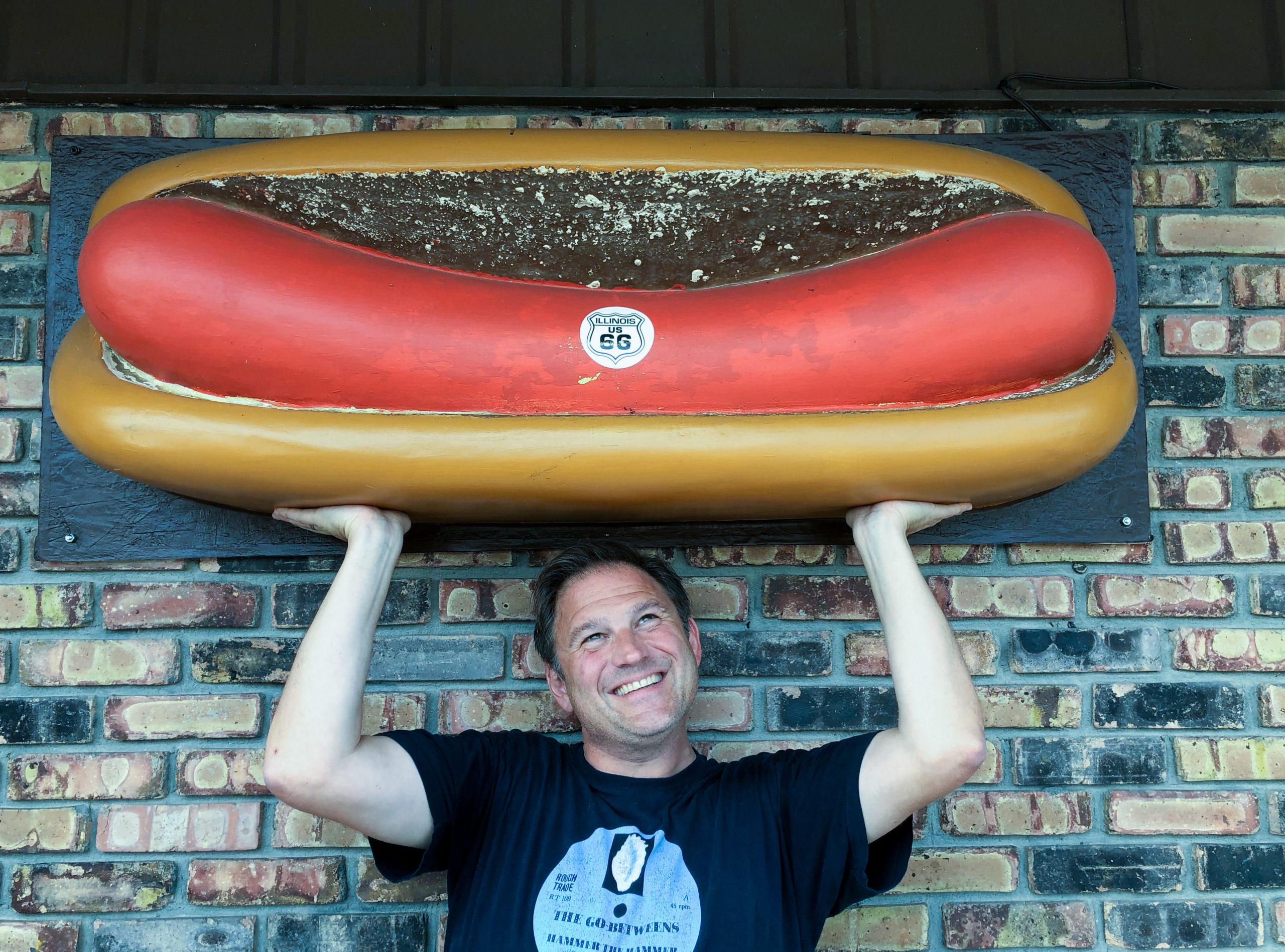 Autor Ralf Johnen stemmt einen Hotdog im Restaurant The Launching Pad an der Route 66 in Illinois