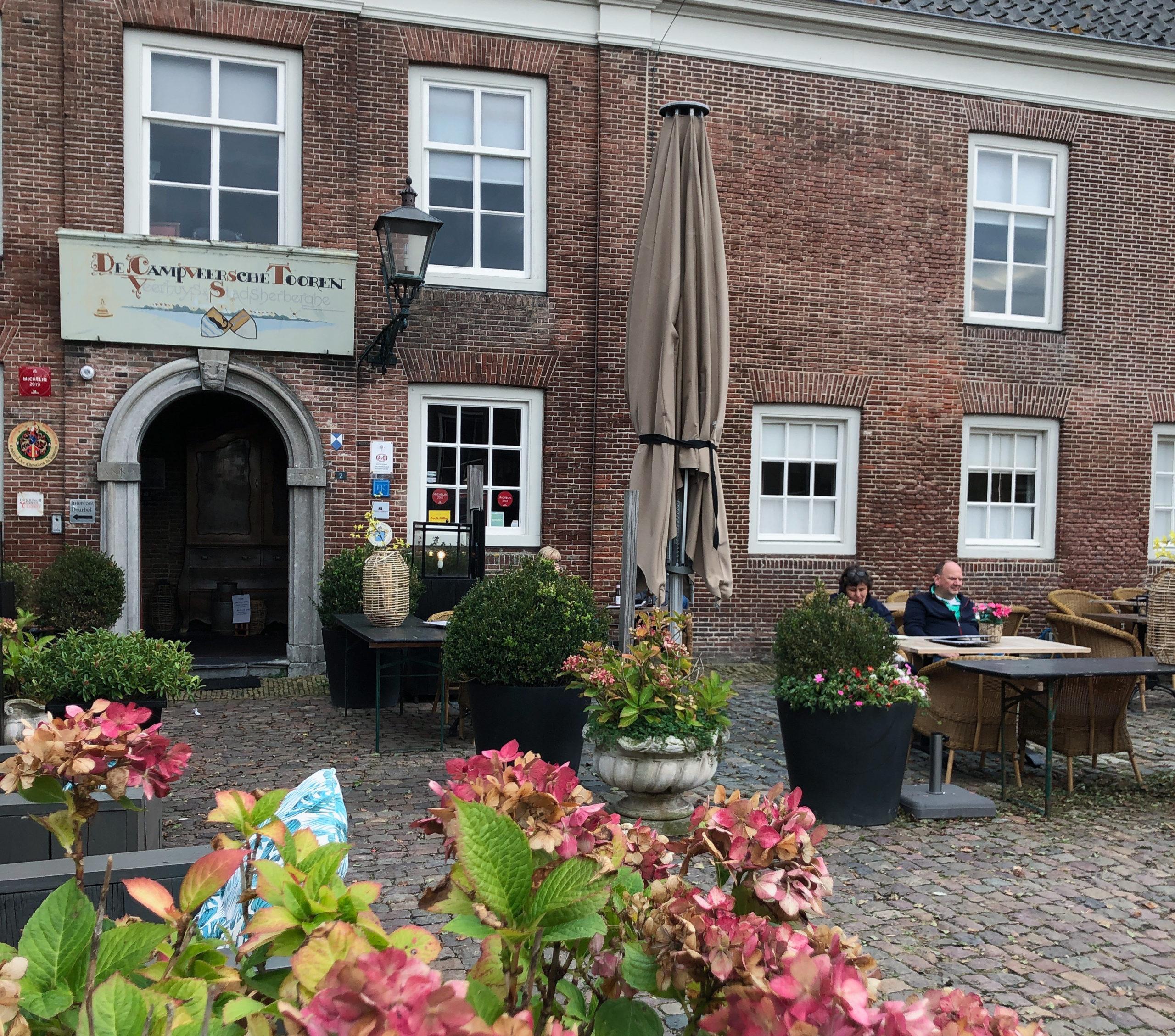 Eingang des Hotels Campveerse Toren mit Blumen und Café