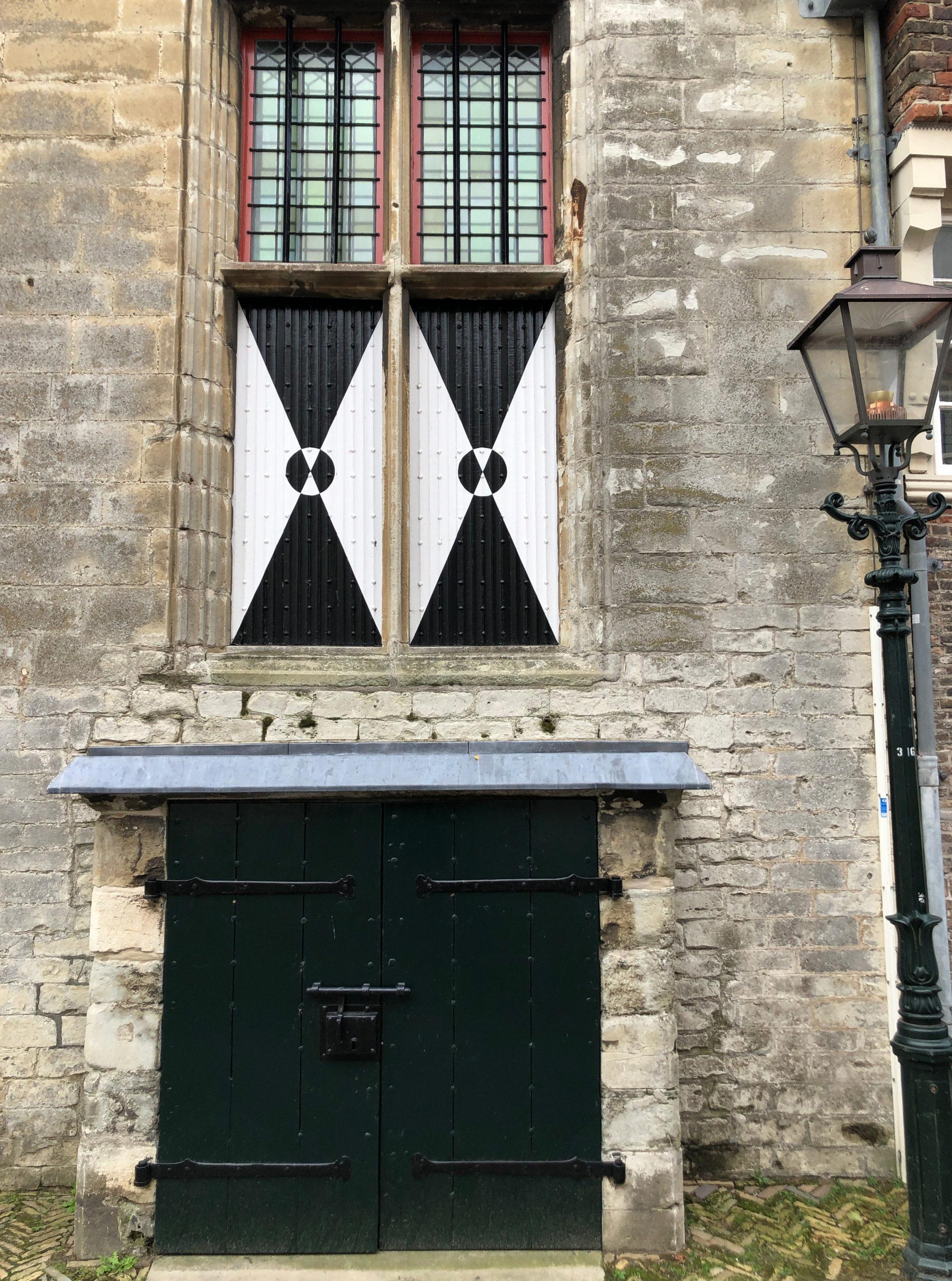 Details eines alten niderländischen Rathauses mit farbigen Fensterläden und alter Laterne