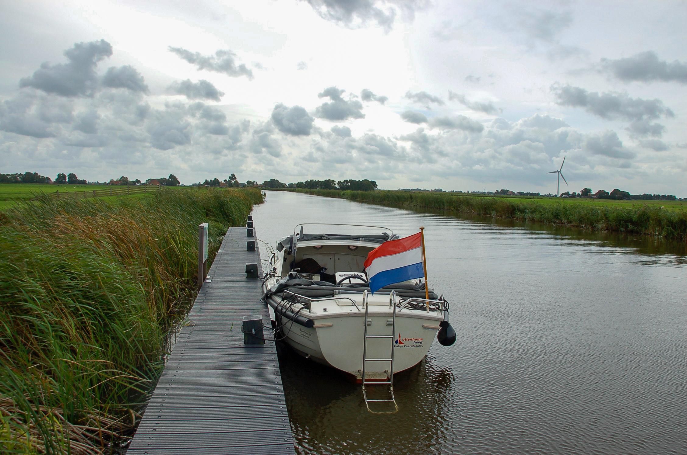 Bootsanleger mitten in der Natur Frieslands mit Kanal und Windrad