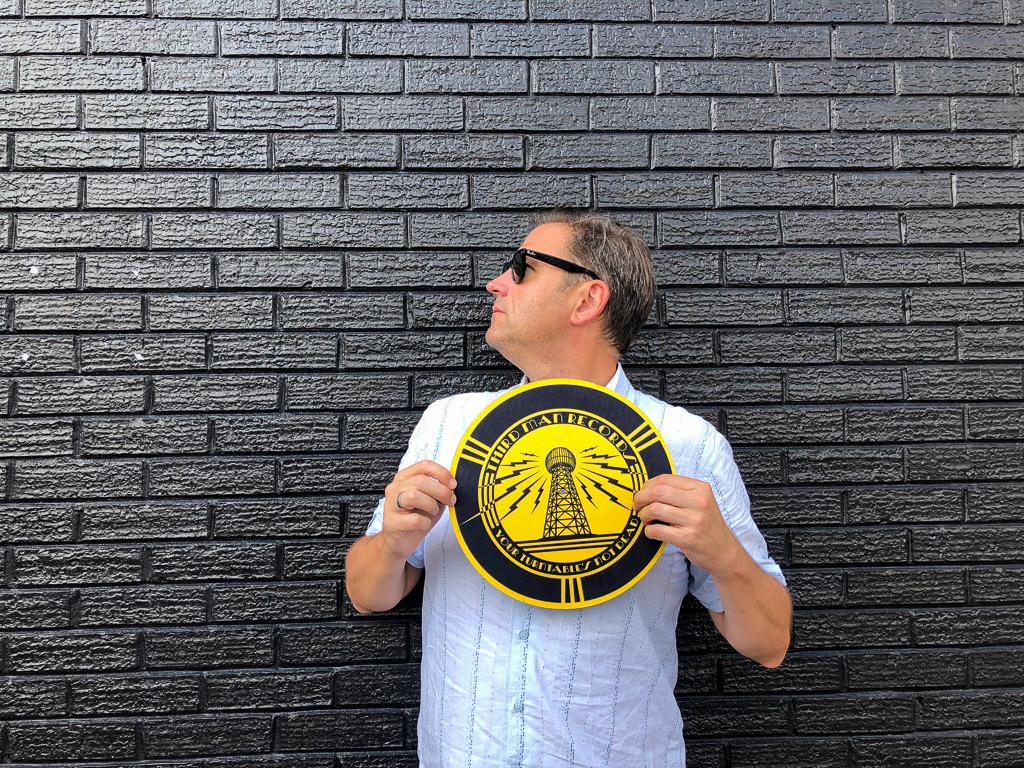 Blogger Ralf Johnen mit einem Plattentellermatte von Third Man Records in Memphis vo riner schwarzen Wand