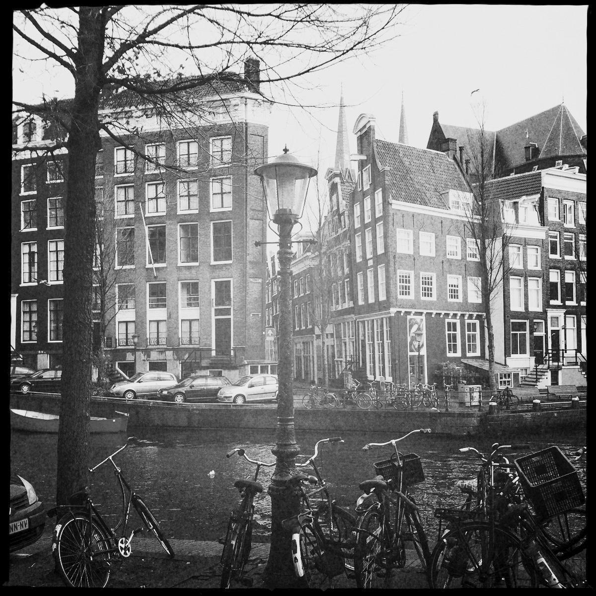 Amsterdam wie im Bilderbuch: Fahrräder, schiefe Häuser, Gracht und Laterne