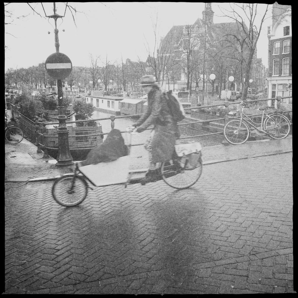 Typisch Holland: Frau mit Bakfiets überquert Brücke.