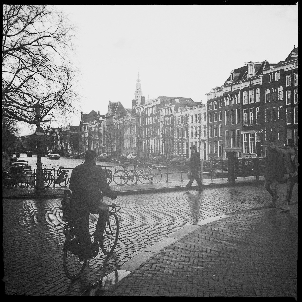 Fahrradfahrer im Grachtengürtel mit der Westerkerk im Hintergrund