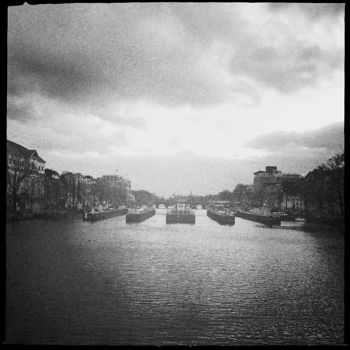 Die Amstel in Amsterdam mit der alten Schleuse und dem Amstel Hotel