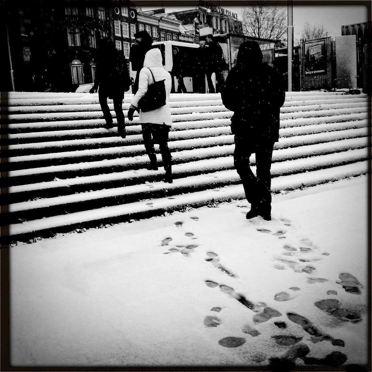 Fußgänger im Neuschnee in Amsterdam.
