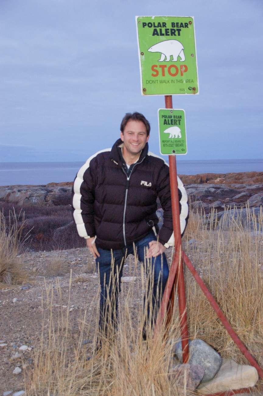 Autor Ralf Johnen vor einem Schild, das vor Eisbären warnt in der kanadischen Provinz Manitoba