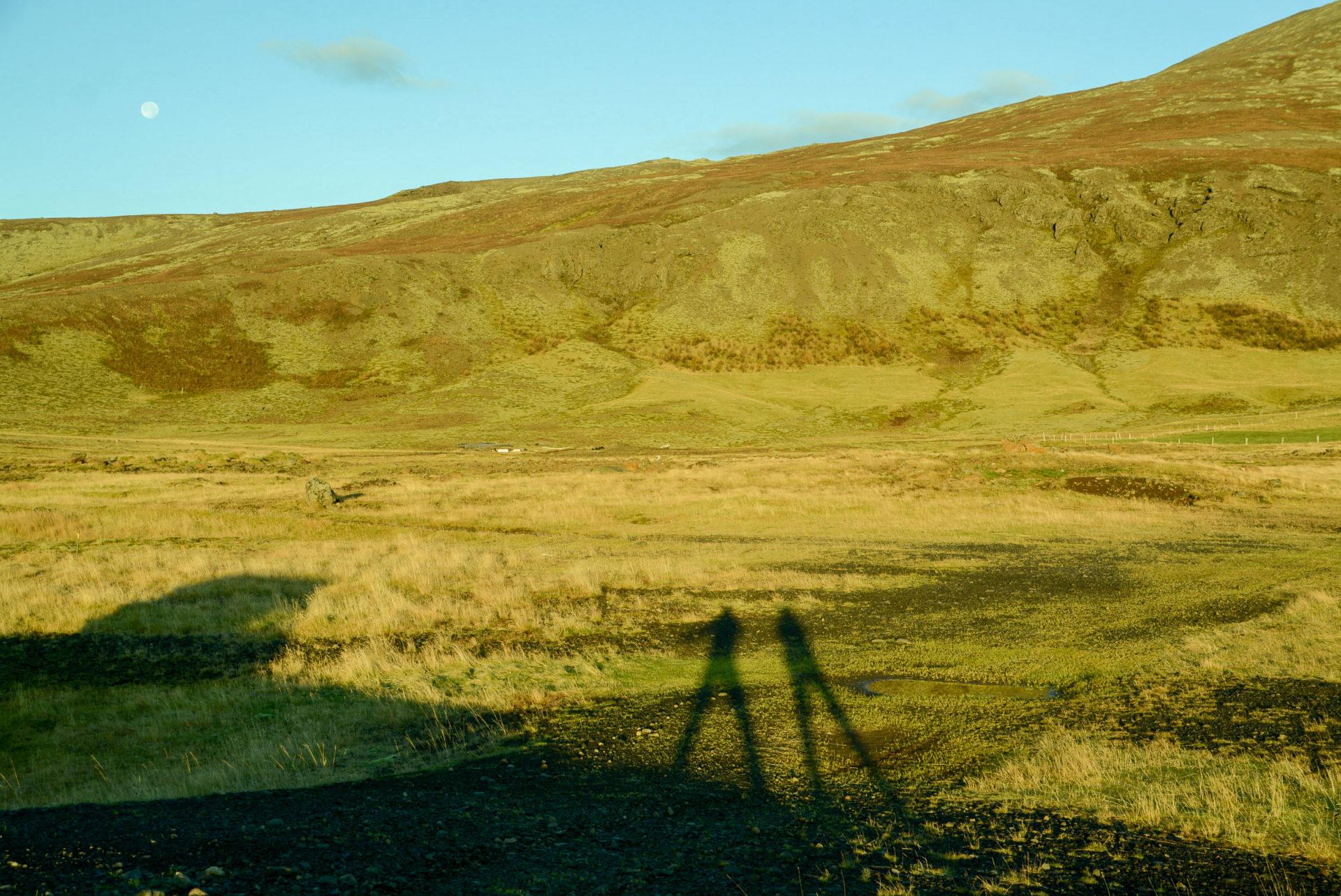 Zwei Schatten auf einer Wiese in Island vor aufgehendem Mond