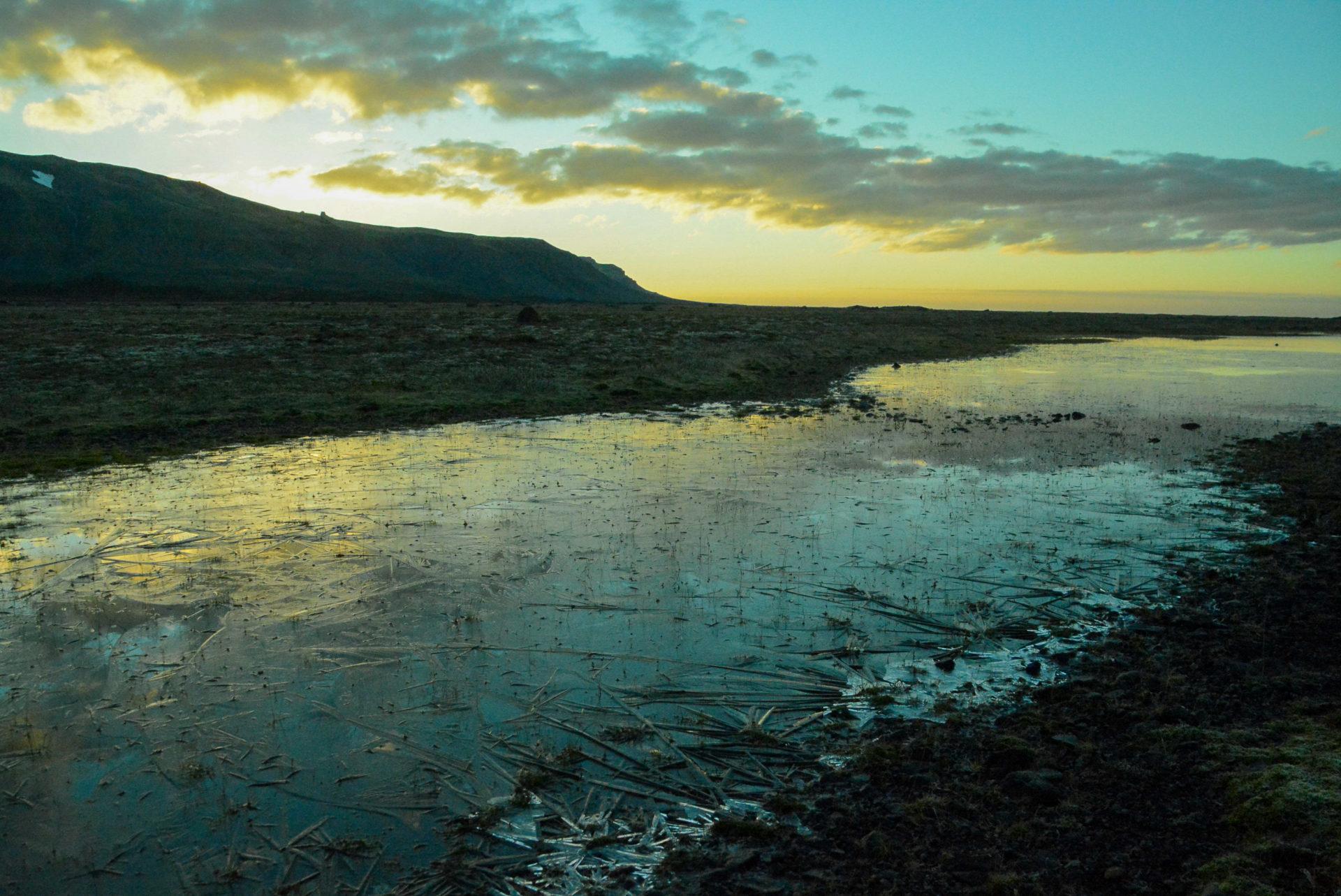 Zugefrorene Pfütze am frühen Morgen nach verpasstem Polarlicht in Island