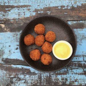 Portion Bitterballen mit Senf auf einem Tisch mit Patina im Strandpavillon Woodstock 69 in Bloemendaal aan Zee