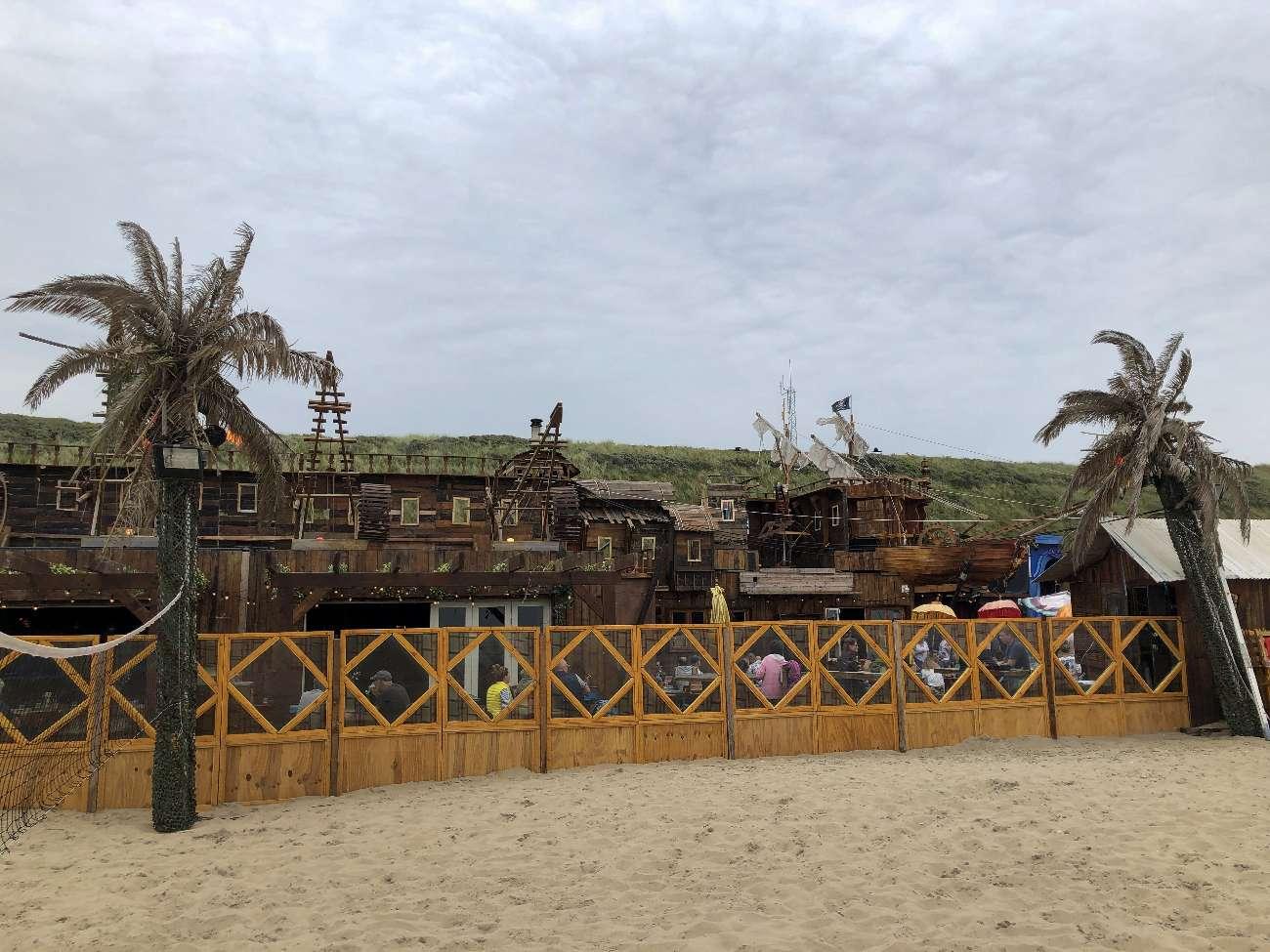 Palmen und Piratenschiff am Strandpavillon Woodstock 69 in Bloemendaal aan Zee