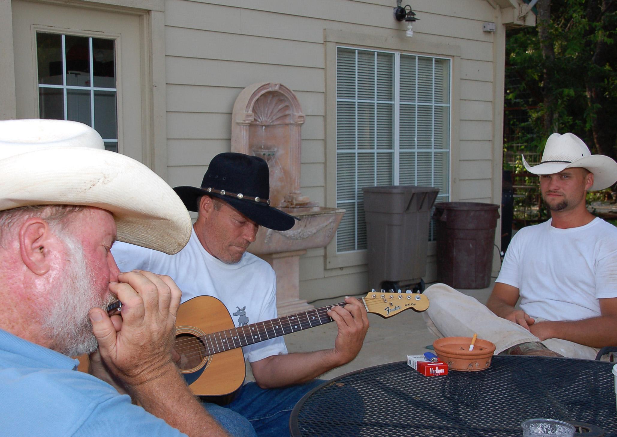 Cowboys musizieren mit Mundharmonika und Gitarre am Lagerfeuer auf der Dude Ranch in Oklahoma