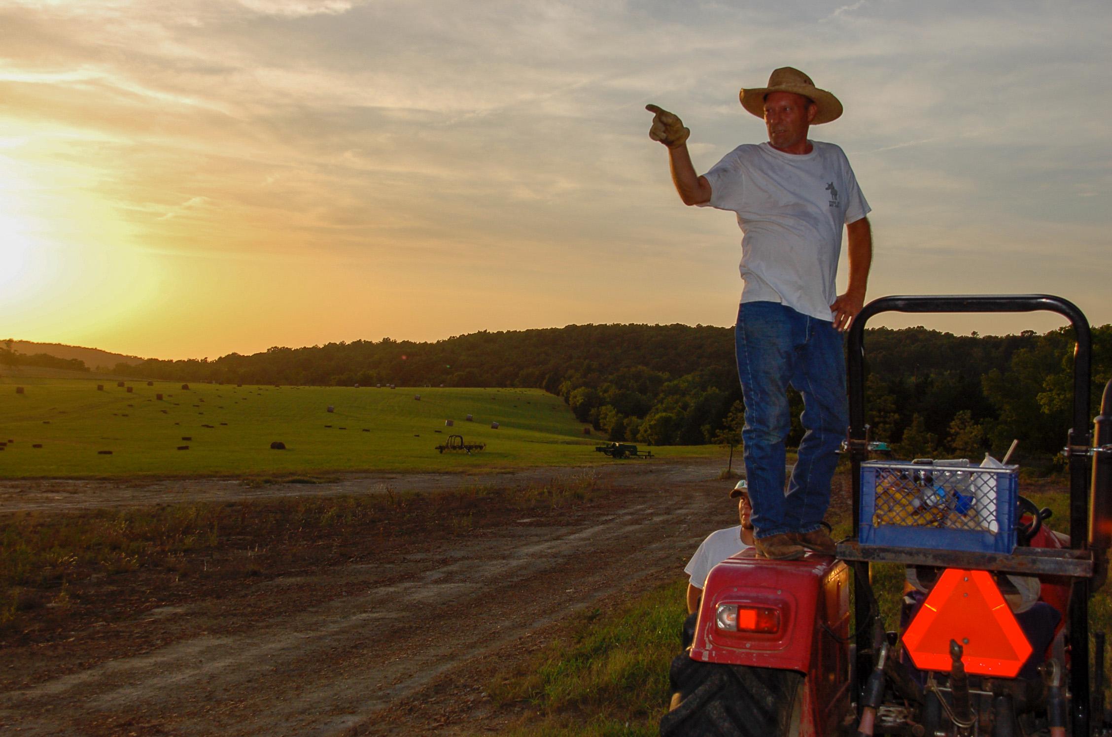 Ein Cowboy steht im Sonnenuntergang auf einem Traktor, während seiner Arbeit auf einer Dude Ranch in Oklahoma