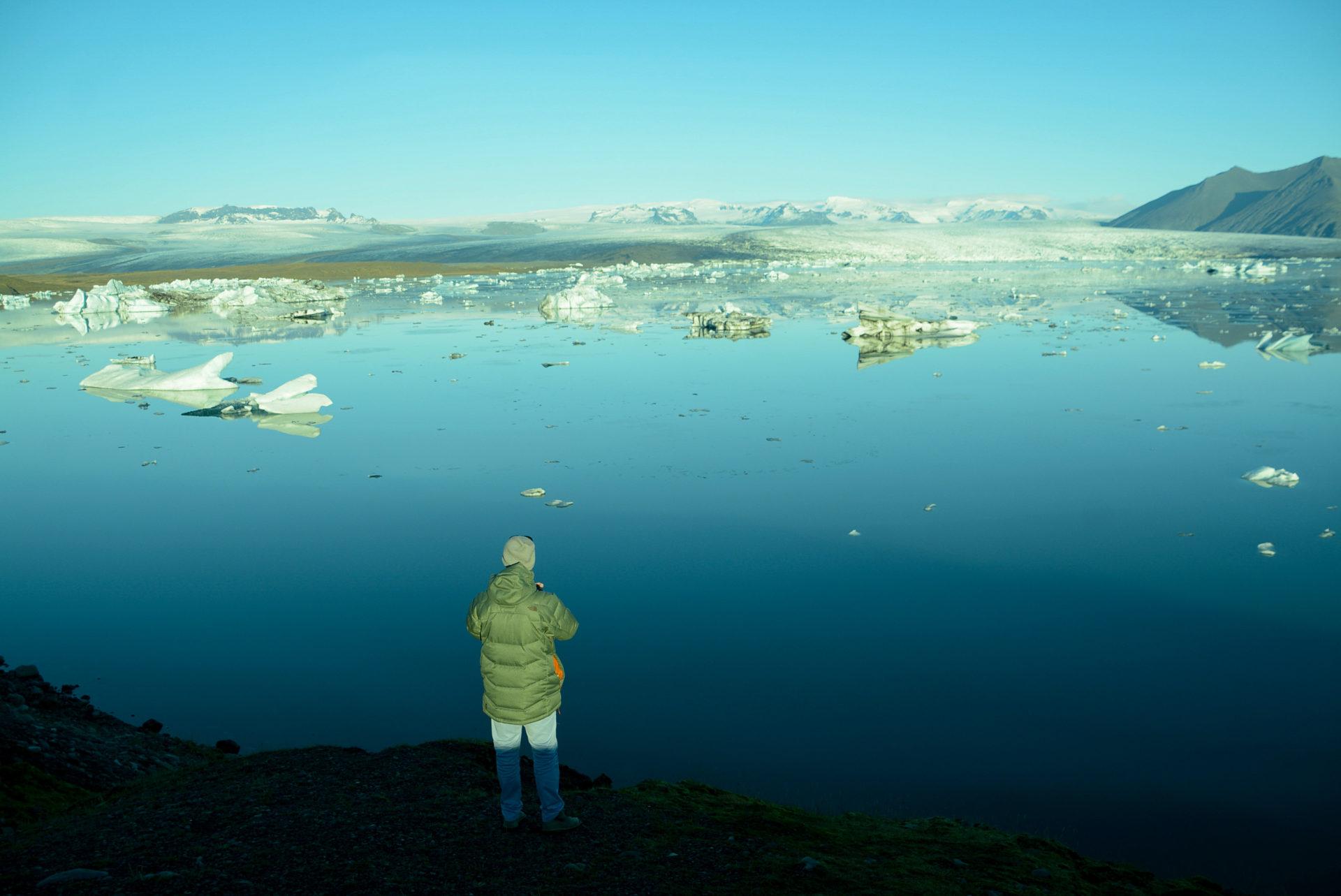 Einsamer Mann vor Gletschersee mit Eisbergen in Jökulsárlón