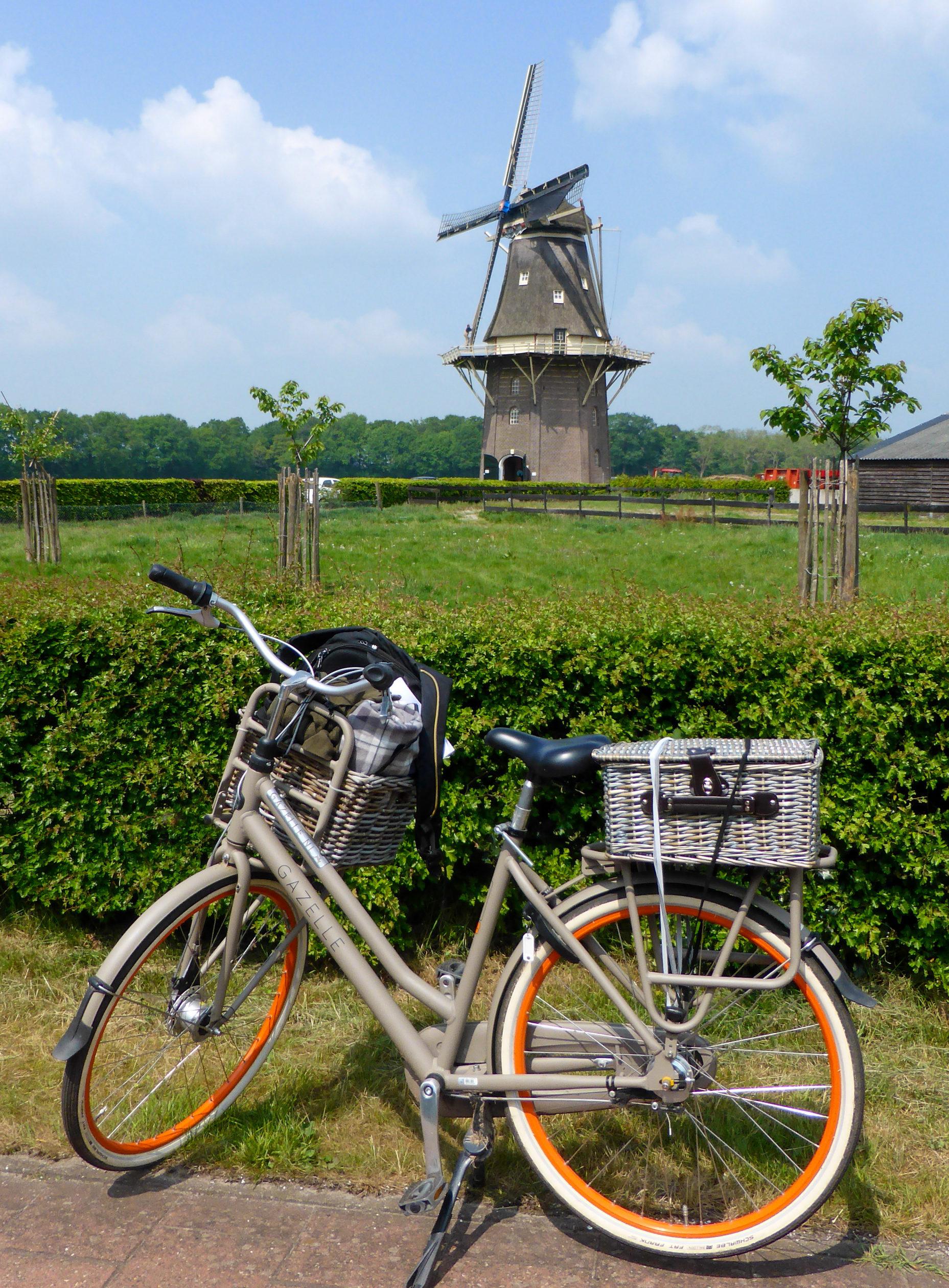 Ein Fahrrad mit Picknickkorb vor einer Windmühle während der Radtour durch Overijssel