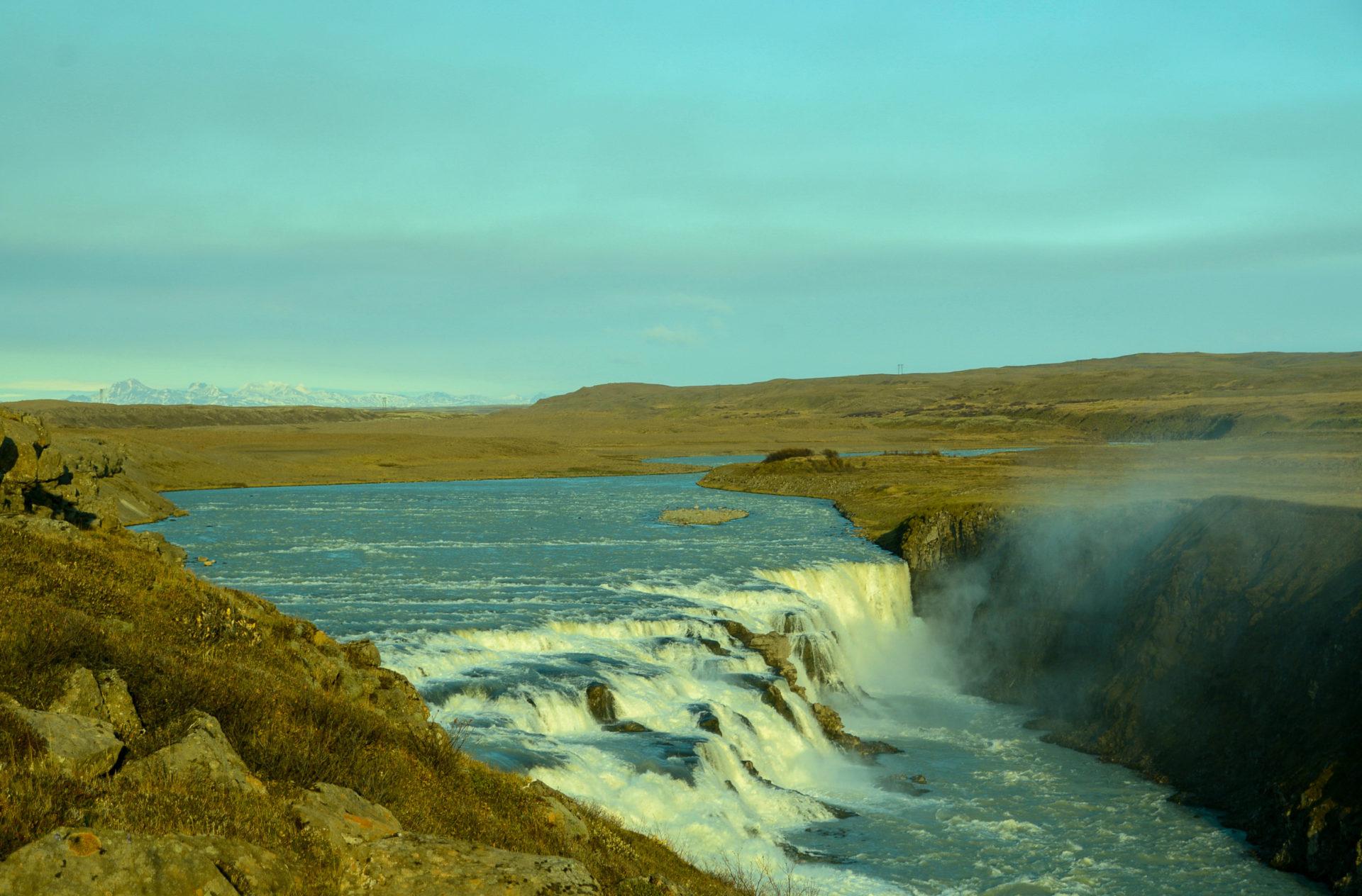 Der Wasserfall Gullfoss im Goldenen Dreieck in Island mit Regenbogen und Bergen