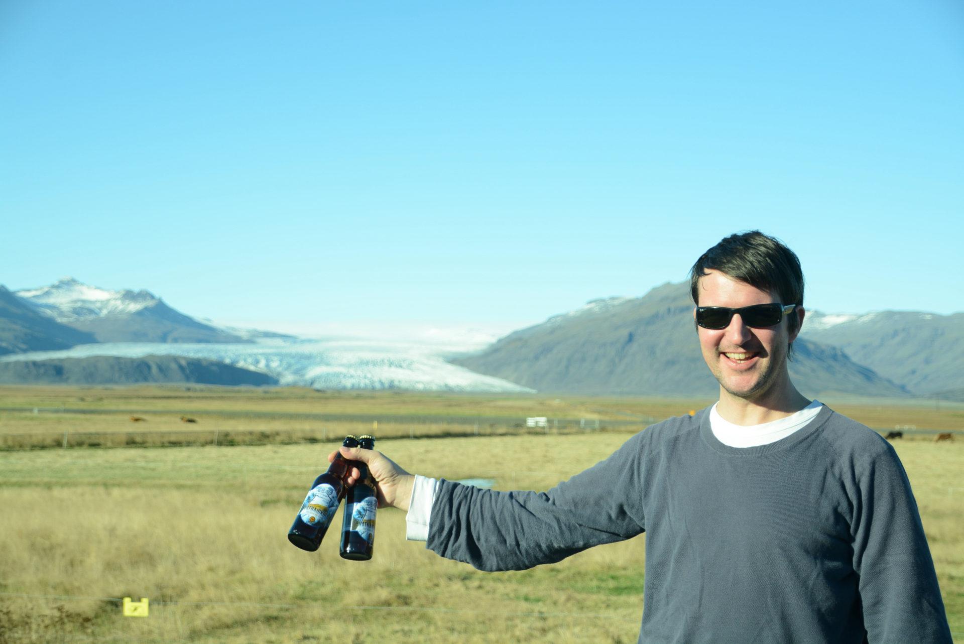 Co-Autor Stefan Weißenborn mit zwei Flaschen Vatnajökull vor einem Gletscher