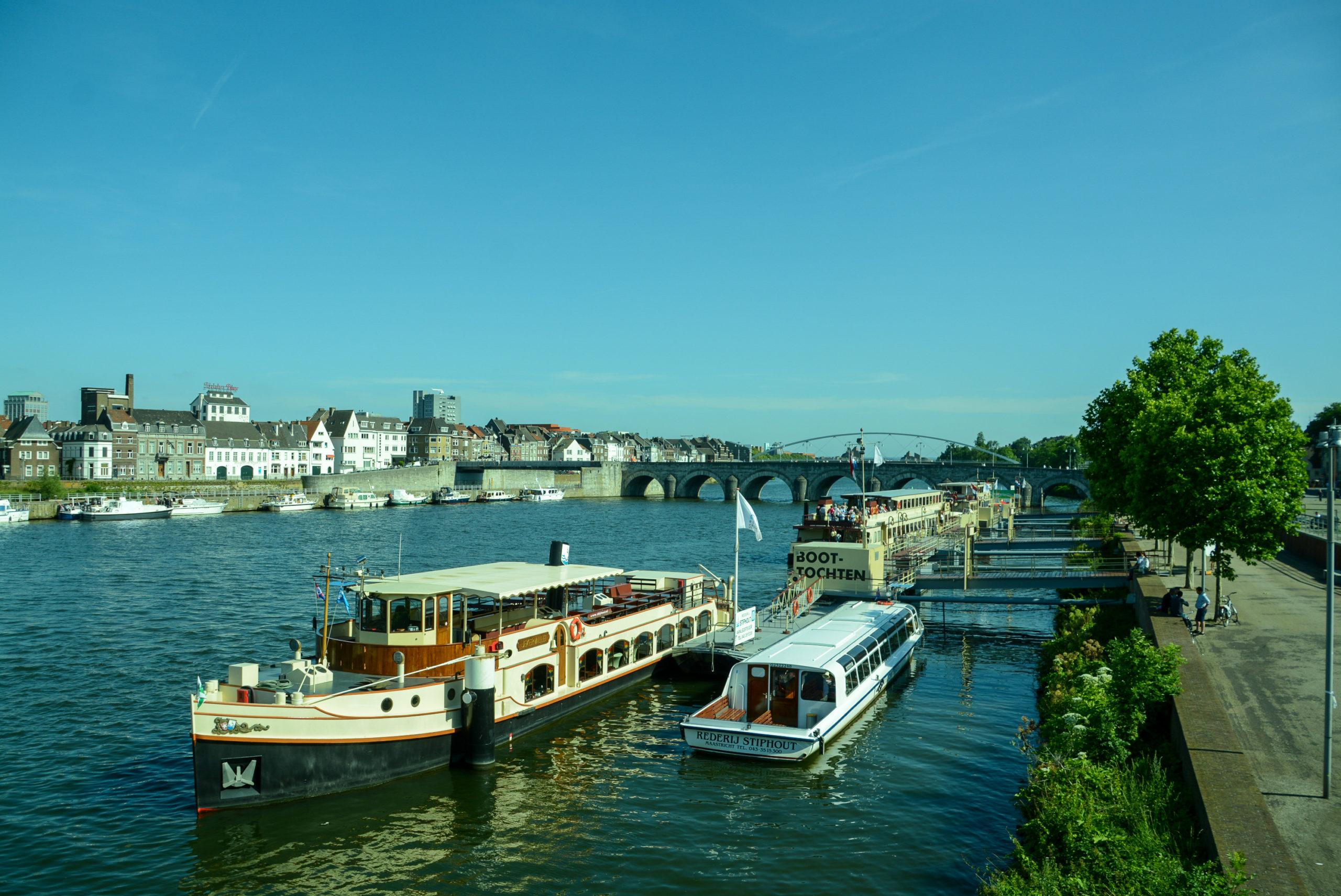 Die Maas in Maastricht mit Ausflugsschiffen und Brücken an einem herrlichen Sommertag