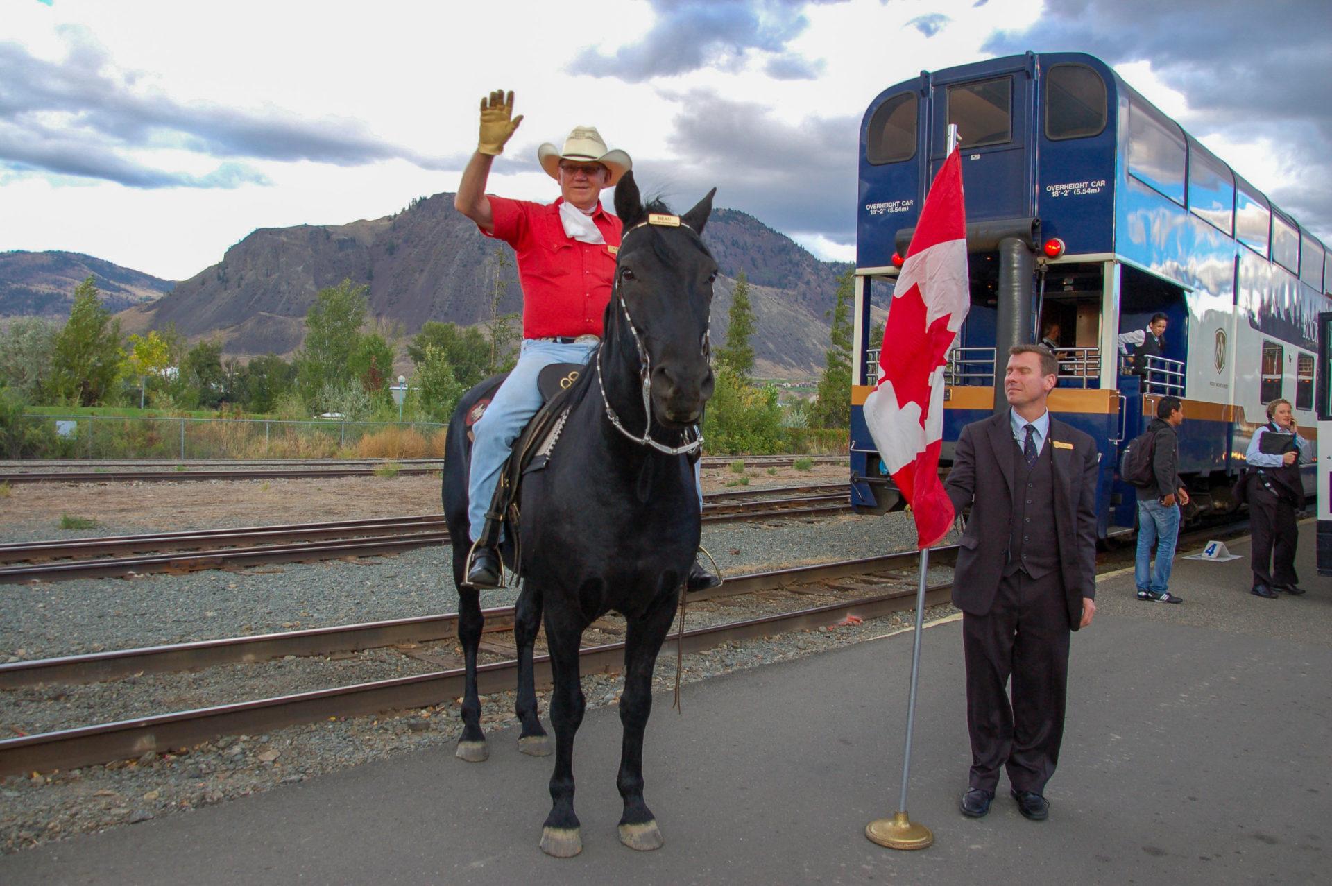 Ein Reiter berüßt die Passagiere des Rocky Mountaineer am Bahnsteig von Jasper in Alberta