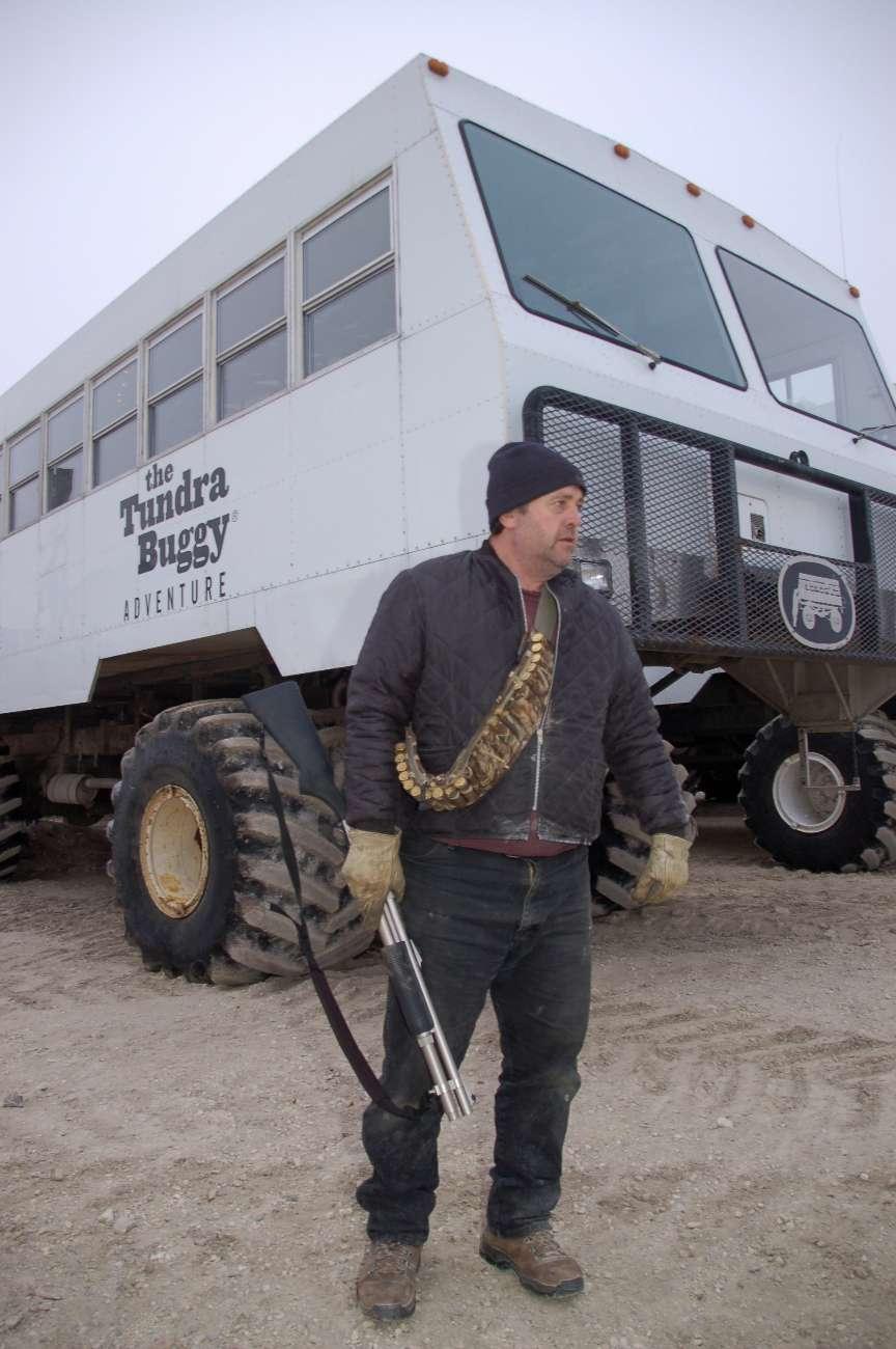 Mann mit Gewehr vor einem Tundra Buggy bei Eisbärensafari