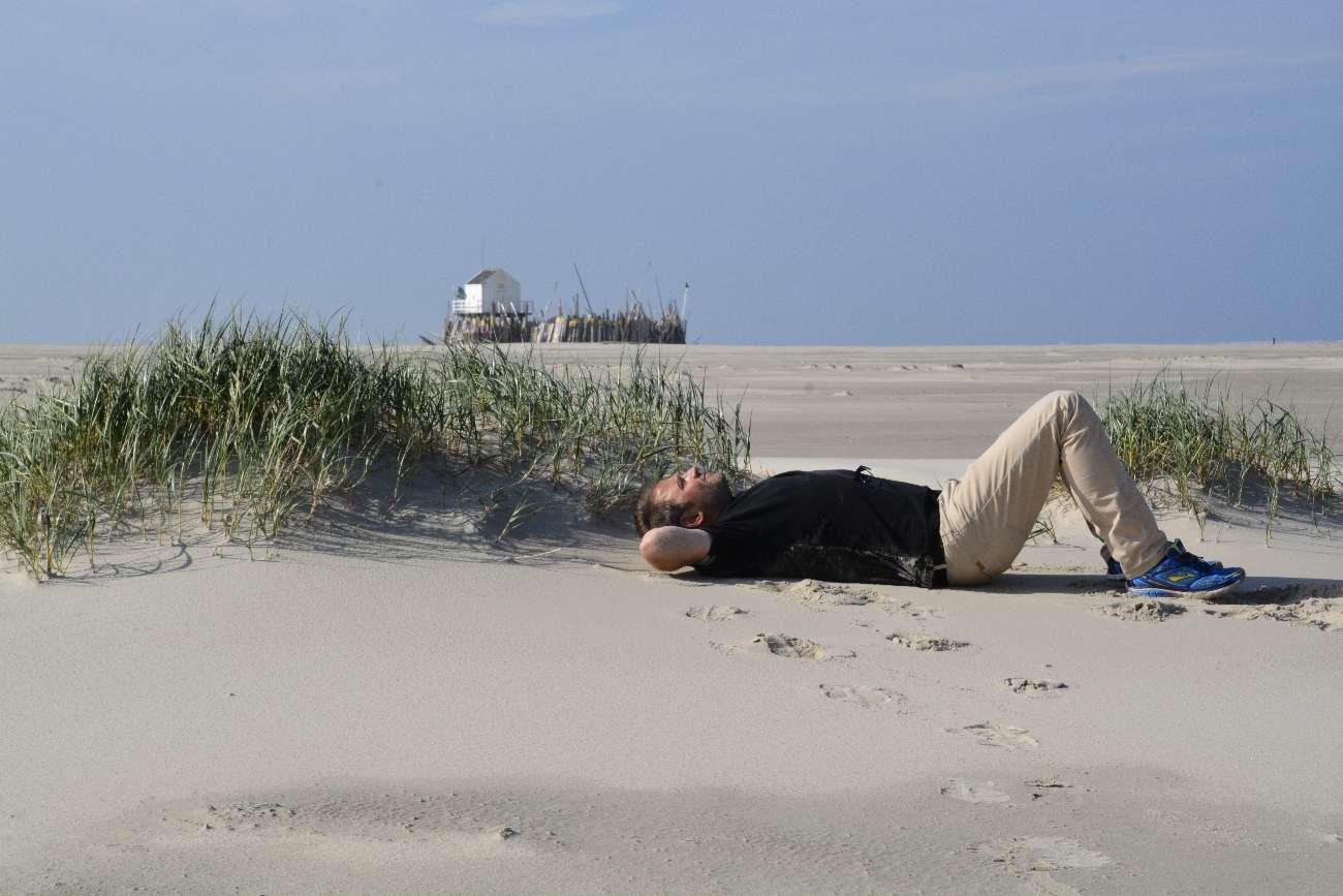 Autor Ralf Johnen liegt im Sand auf Vlieland