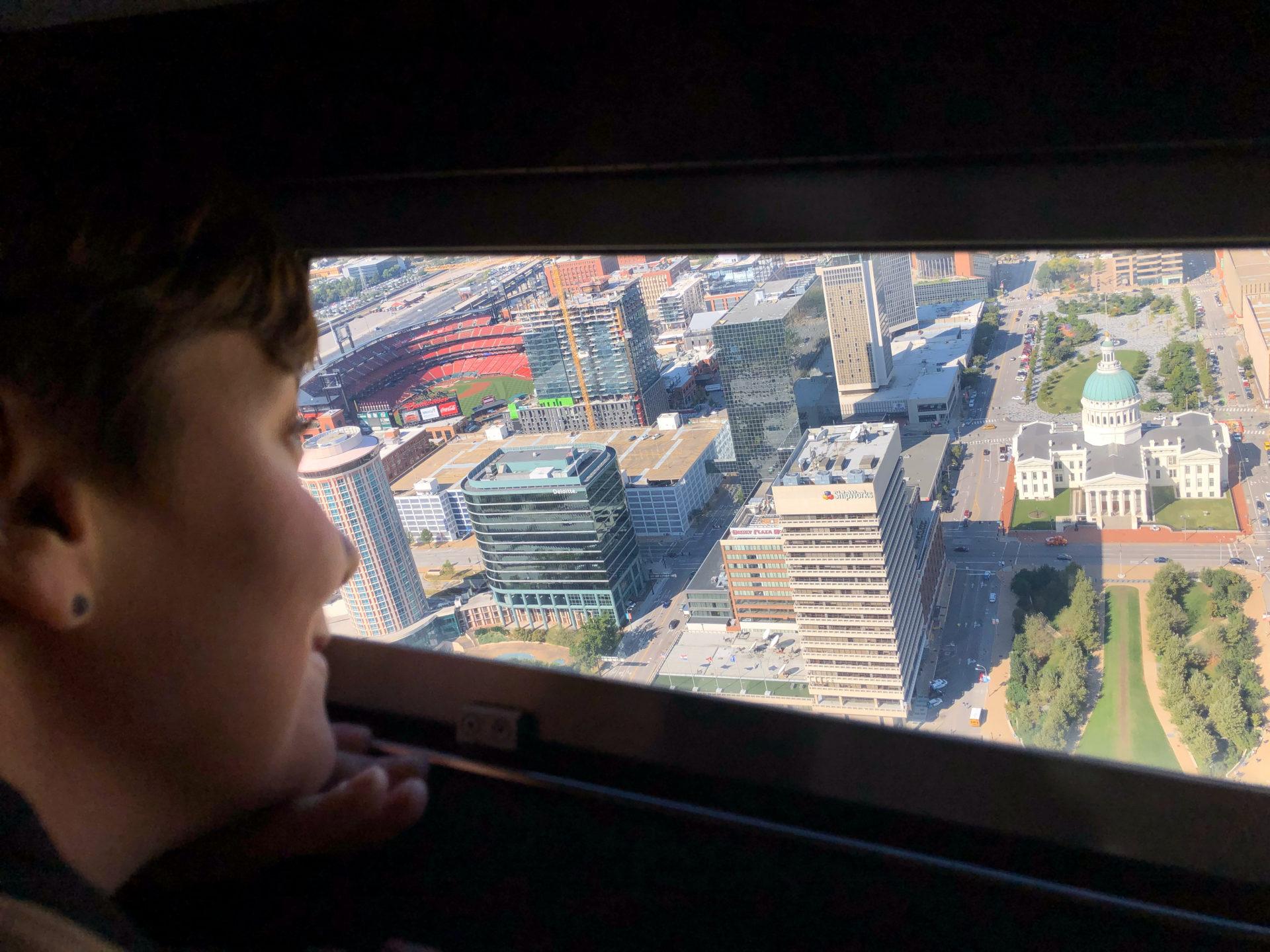 Eine junge Frau blickt vom Gateway Arch auf die Skyline von Saint Louis