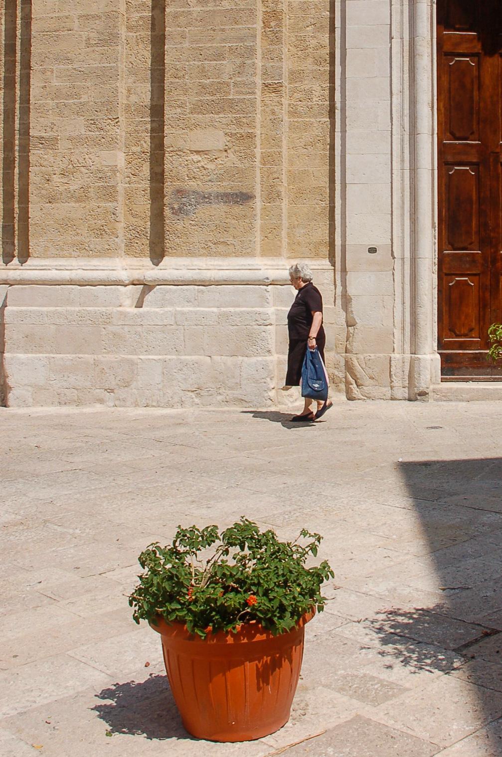 Eine Frau vor der Kirche von Bari mit Blumentopf