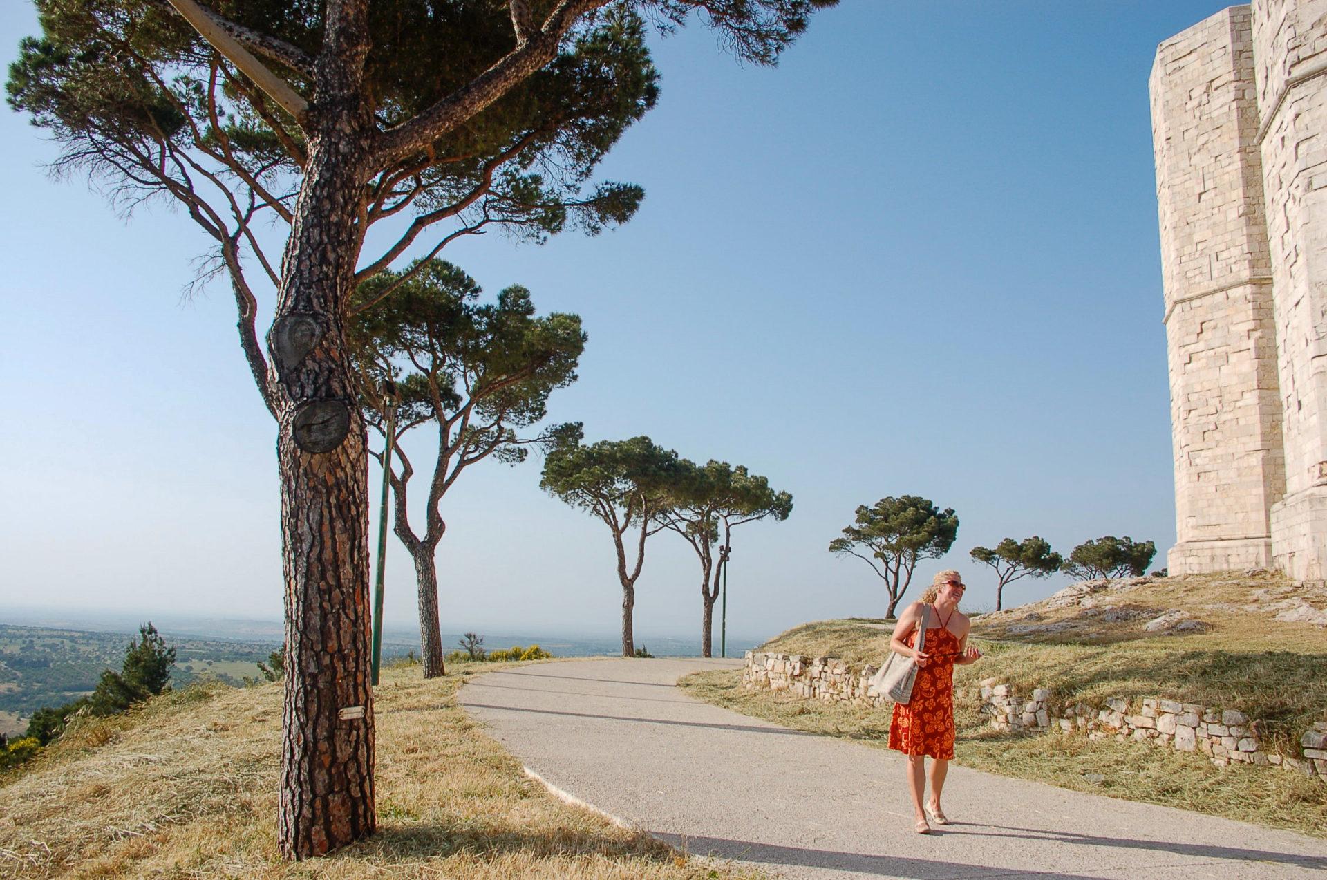 Eine Frau unter Pinien beim Castello del Monte, einer der Topsehenswürdigkeiten in Apulien