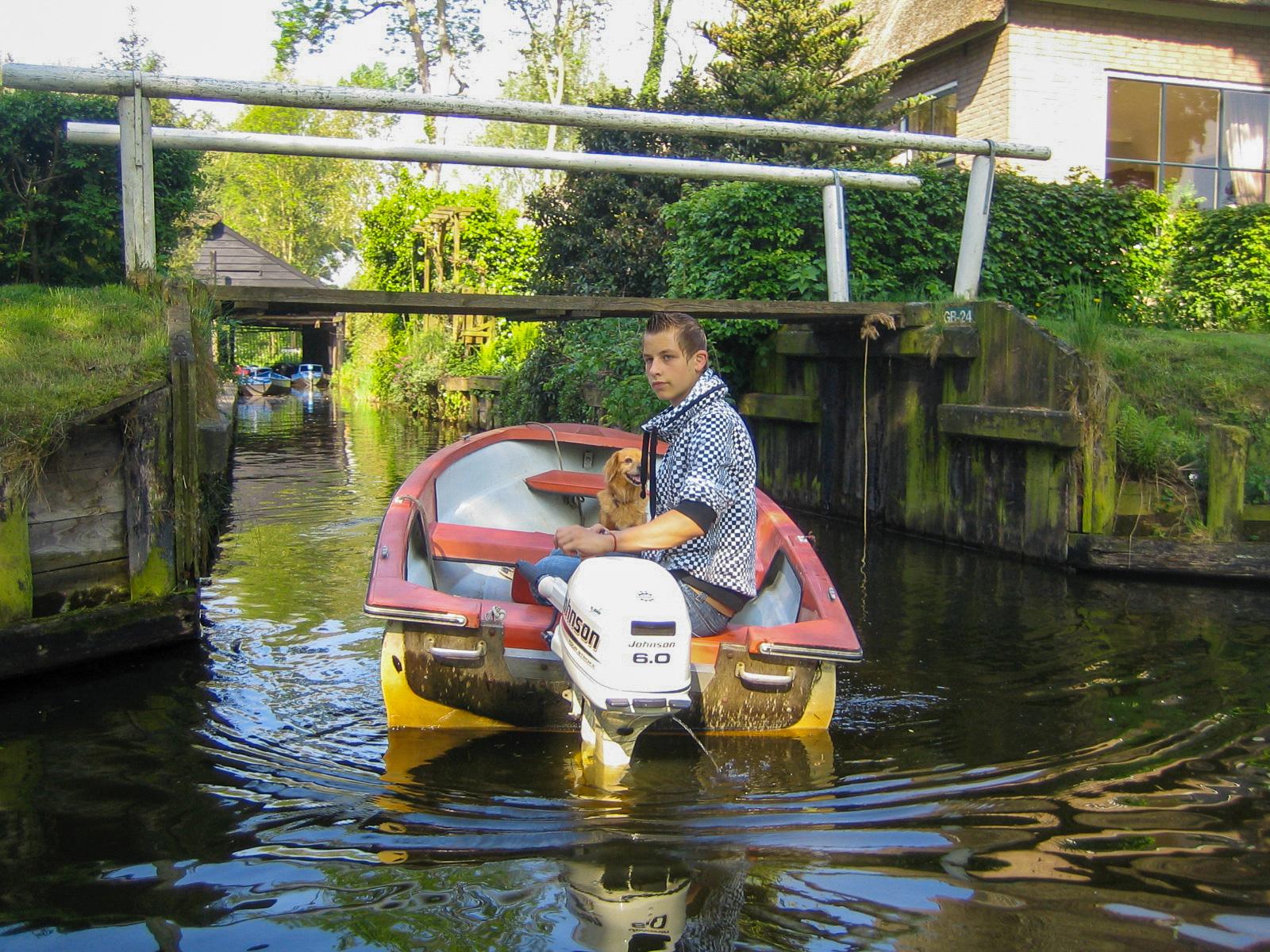 Eine Junge mit Hund in einem Boot auf einer Gracht während einer Bootstour in Giethoorn