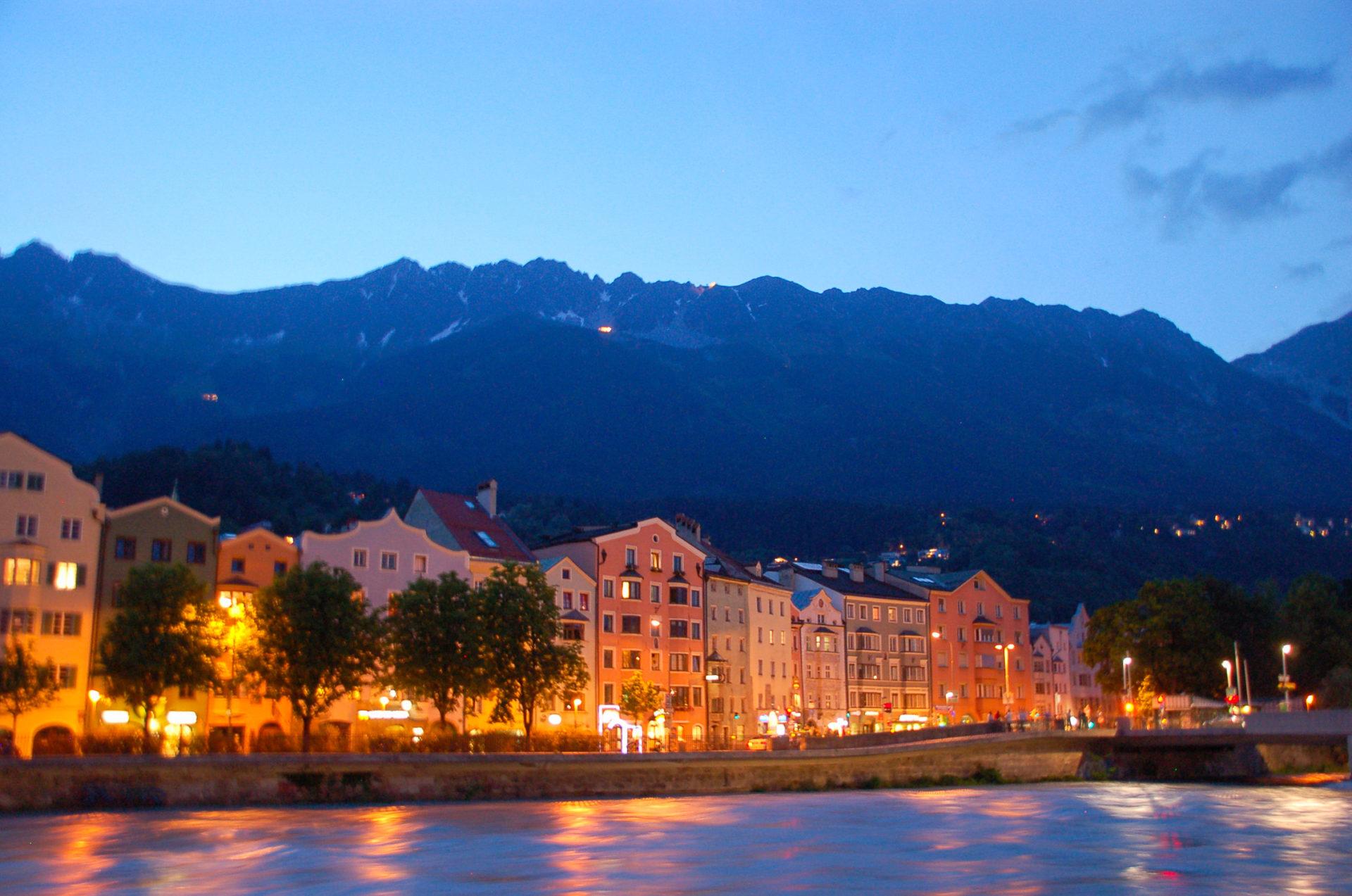 Innsbruck bei Nacht mit Blick auf den Inn und die Berge